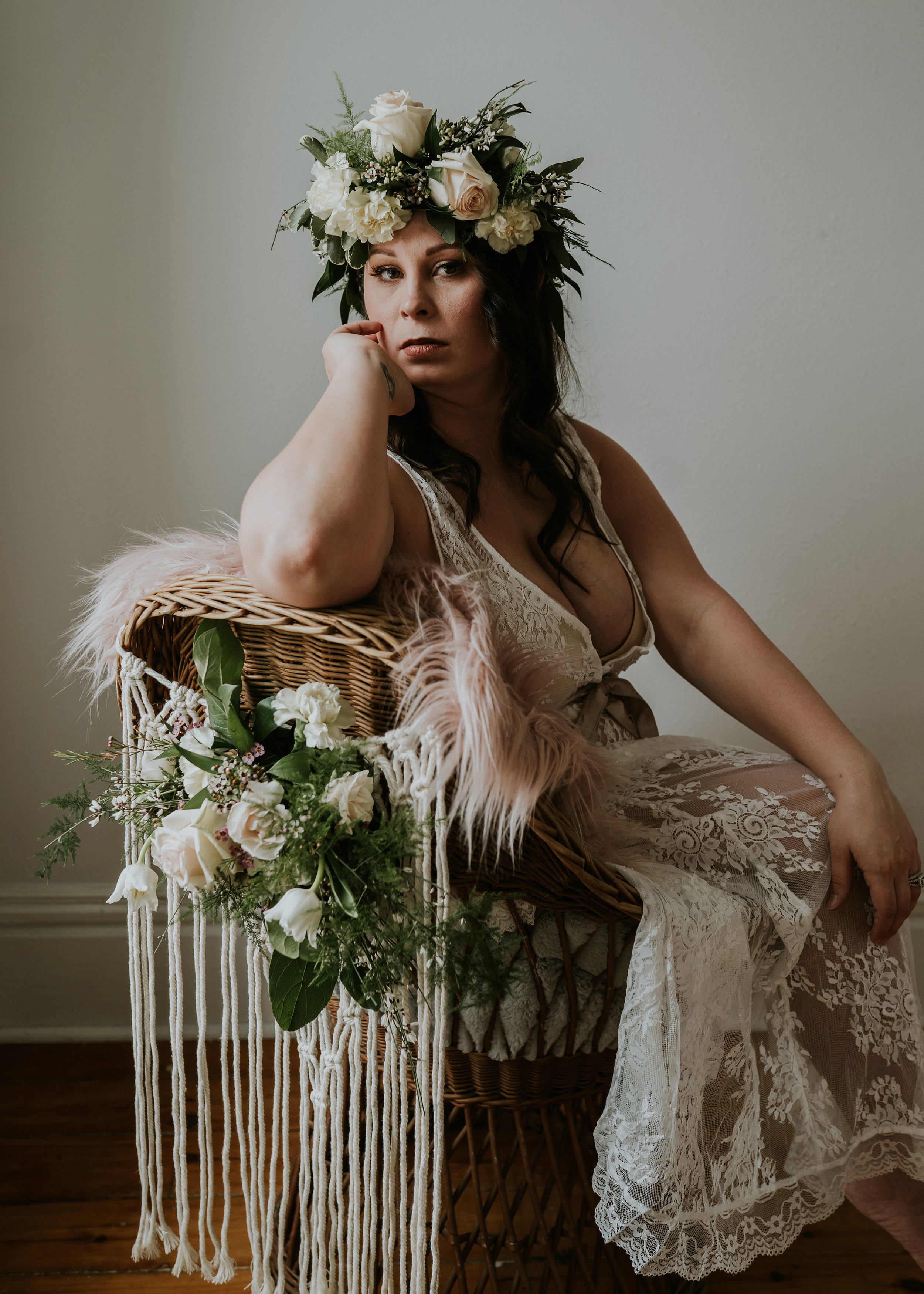 new mother photo shoot, woman wears lacy lingerie from Des Moines and sits in wicker boho chair with floral accents by Lavender Blue Floral, styled photos and design by Lavender Blue