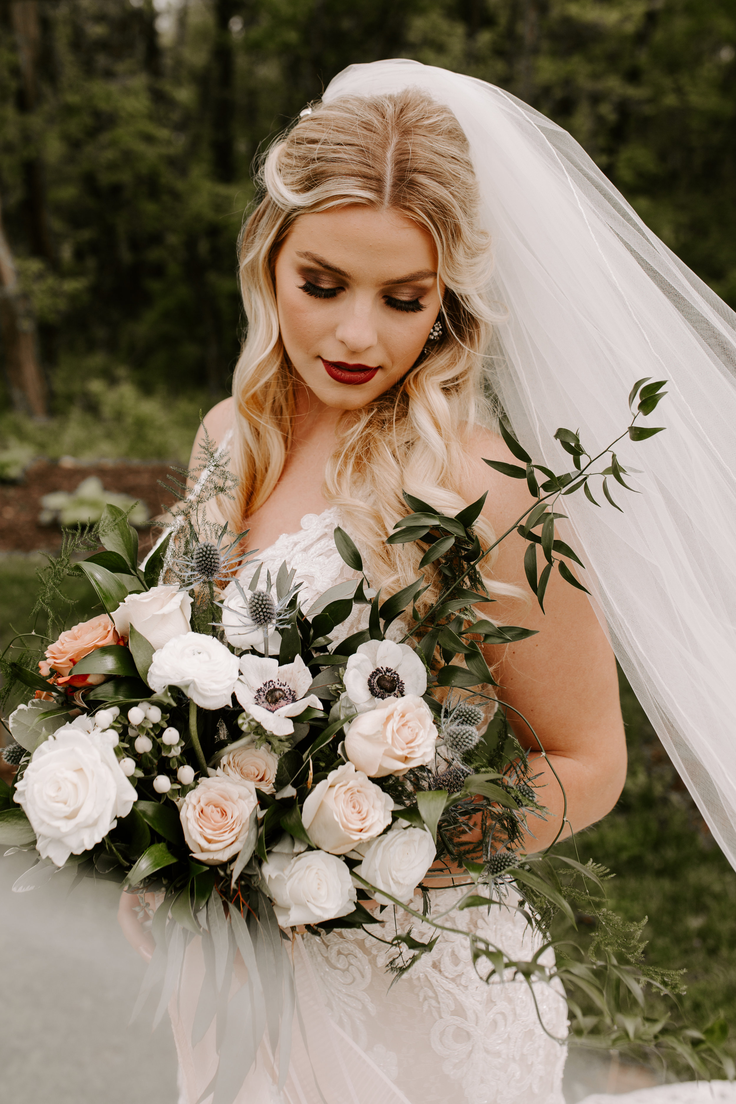 Bride with bouquet in blush at Country Lane Lodge, holding bouquet with anemones and blush roses, bridal gown from Weddings by Design in West Des Moines