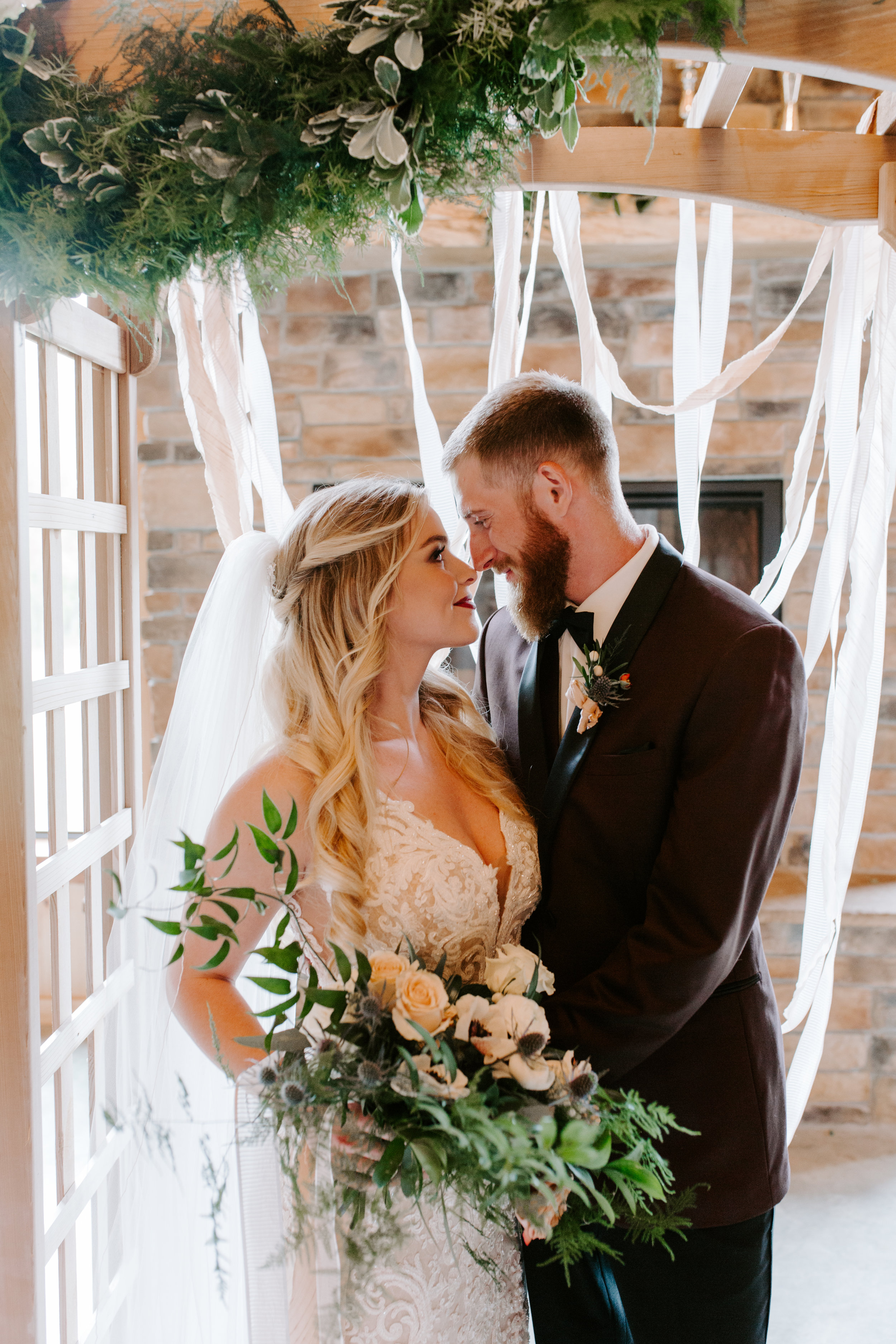 Bride and groom at Country Lane Lodge in Iowa, under arbor at wedding ceremony styled by Lavender Blue, holding blush and cream flower bouquet