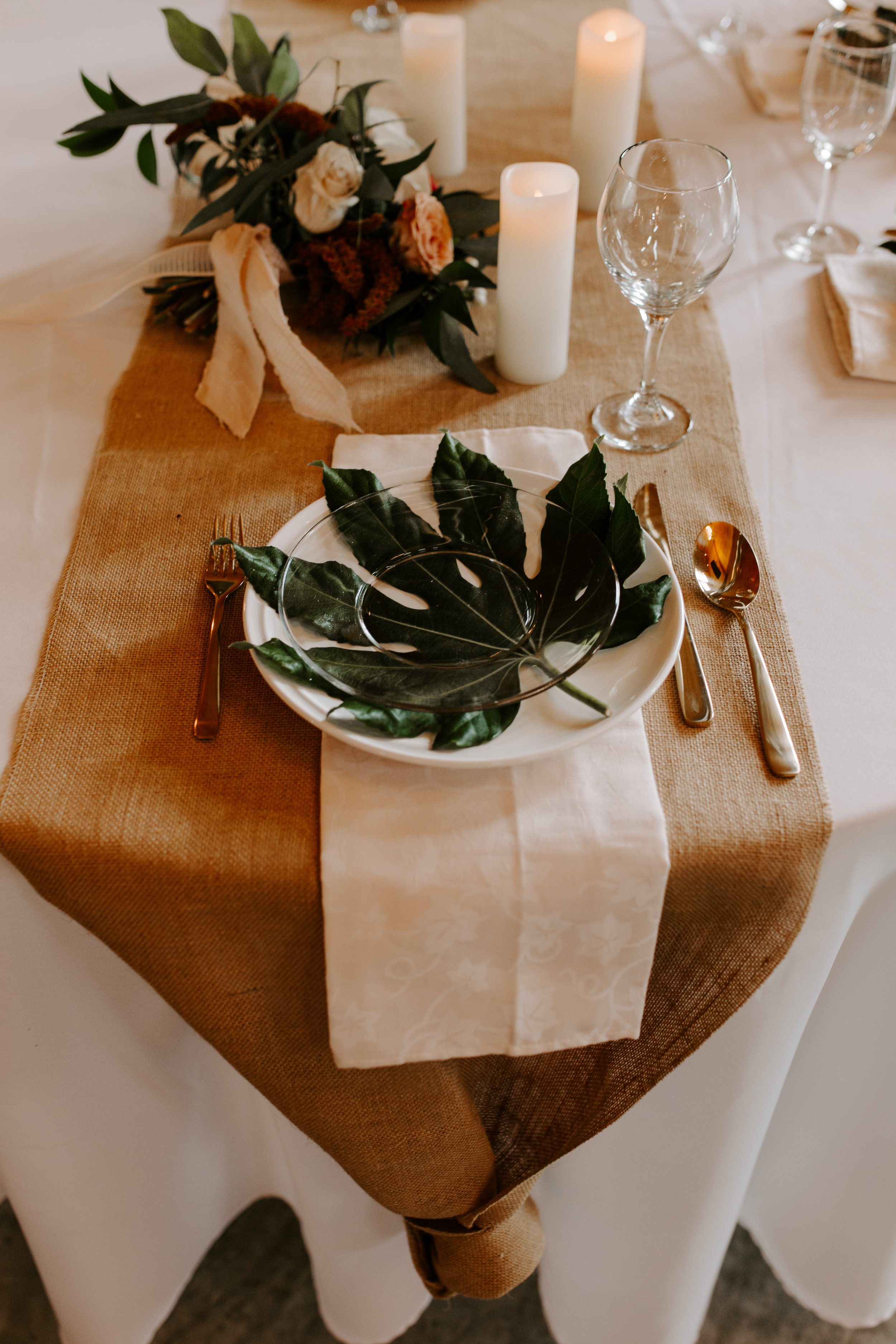 Styled wedding reception by Lavender Blue with large leaf motif on white plate and candles with flowers in white vase