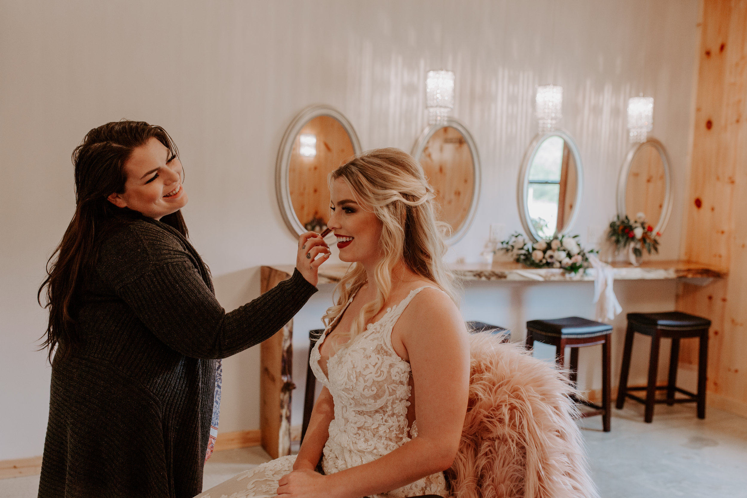 Bride getting her hair and makeup done in bride room at Country Lane Lodge in Iowa, smiling and having blush applied by makeup artist