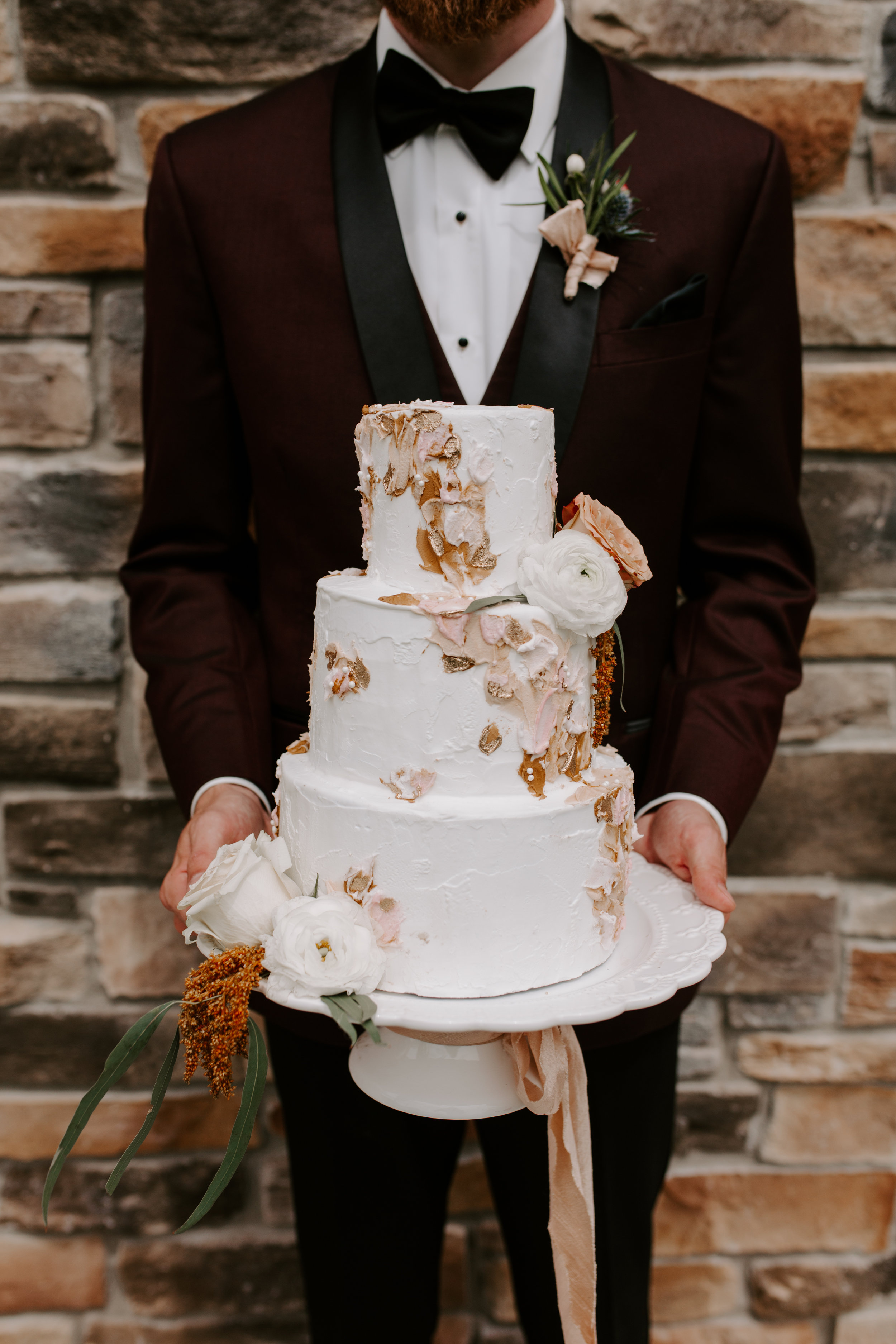 3 tier faux wedding cake being held by groom at County Lane Lodge in Iowa, wrapped with ribbon from Lion Ribbon and styled by Lavender Blue