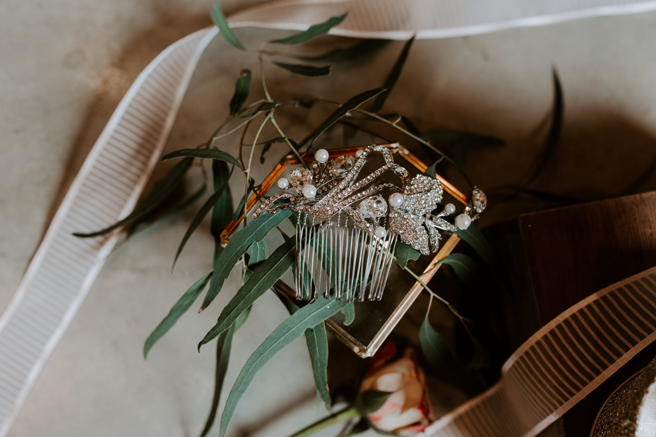 Brides jeweled hair comb in photo with eucalyptus and ribbons from Lion Ribbon company, styled by photo stylist Lavender Blue