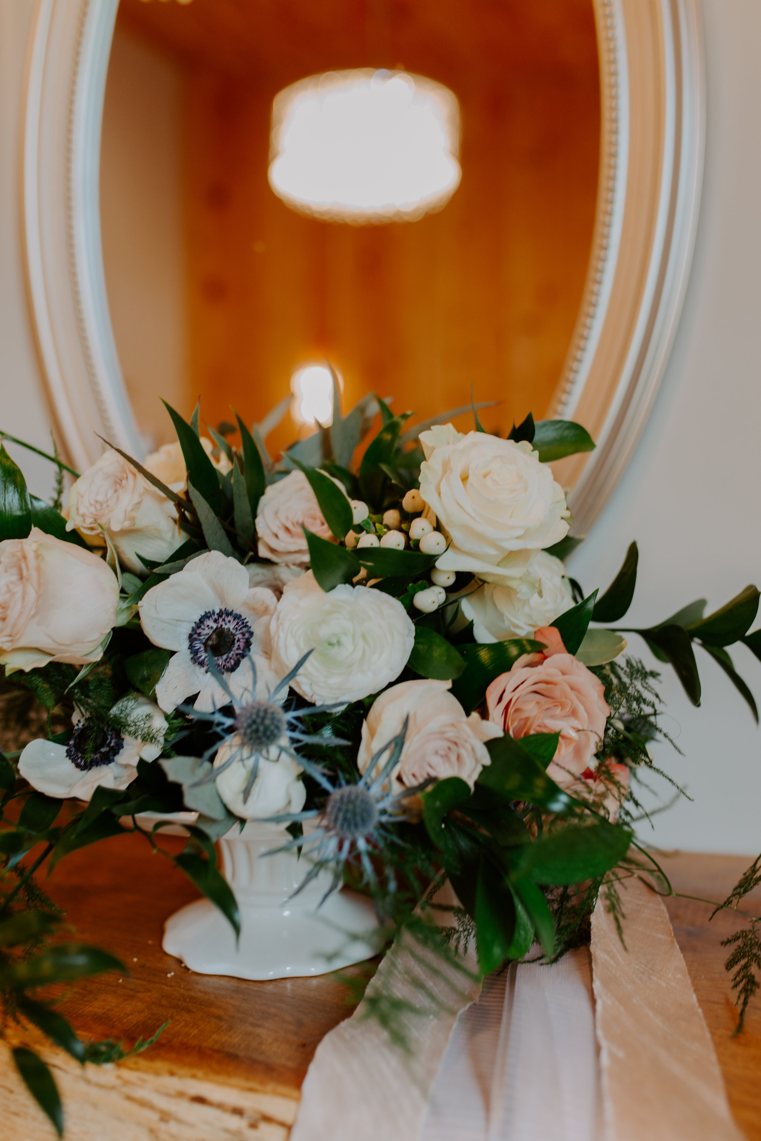 A bridal bouquet with cream and white flowers, blush rose, blue thistle, tied with satin ribbon in peach color, white berries and eucalyptus as accent for wedding at Country Lane Lodge