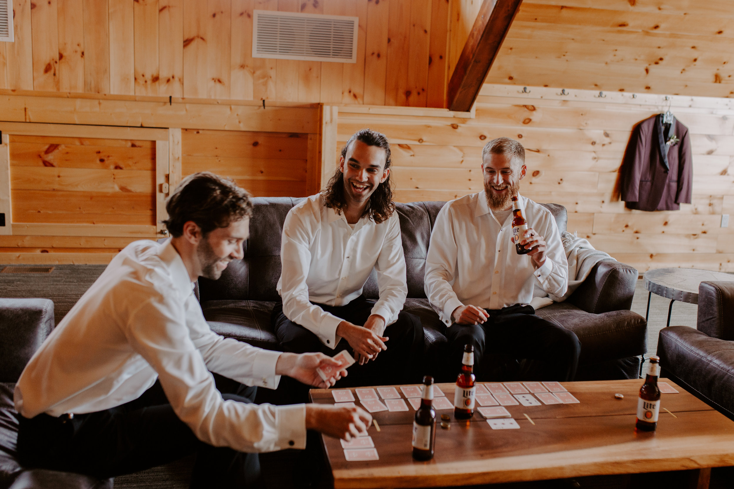 Groomsmen play cards and enjoy a beer while relaxing in their own area for getting ready at Country Lane Lodge in Adel Iowa. They are wearing white shirts and sitting on a leather couch, smiling and having fun while they wait for the wedding ceremony to start