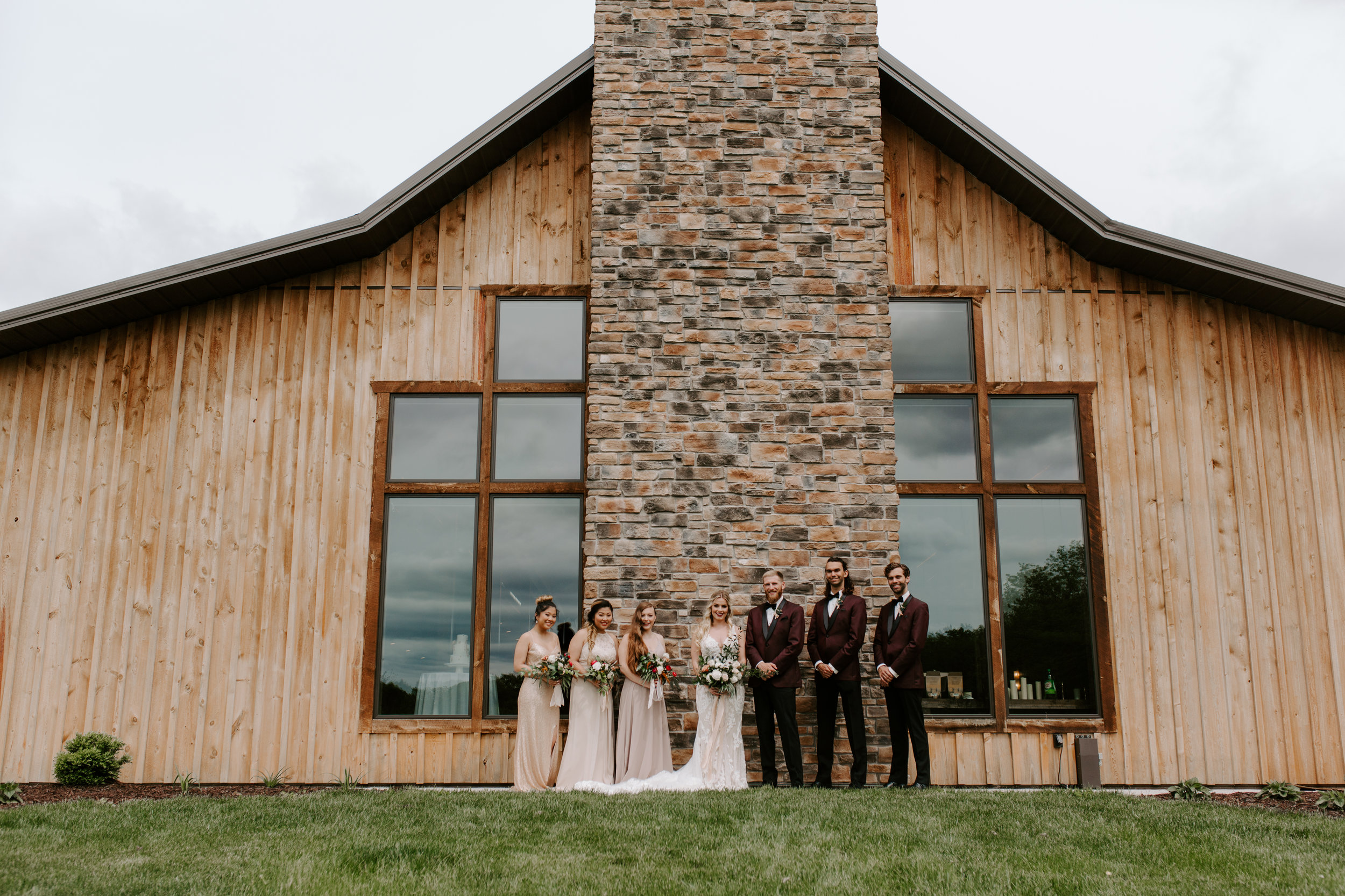 barn venue in Adel iowa for weddings and events, exterior chimney in brick shows behind wedding party posing in blush and cream dresses, with burgundy color tuxes