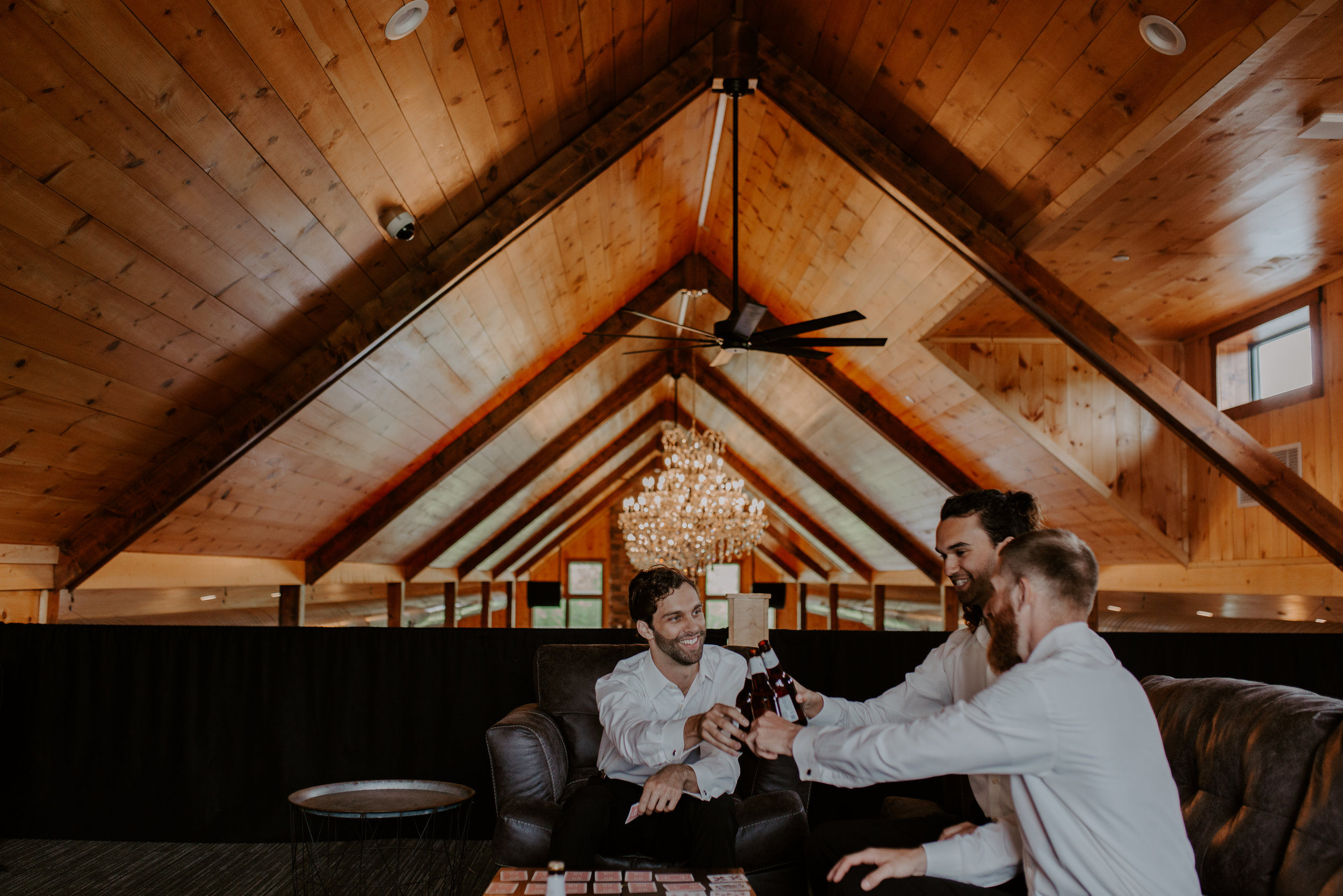 groomsmen playing cards in room where they are getting ready for wedding and having a drink and smiling