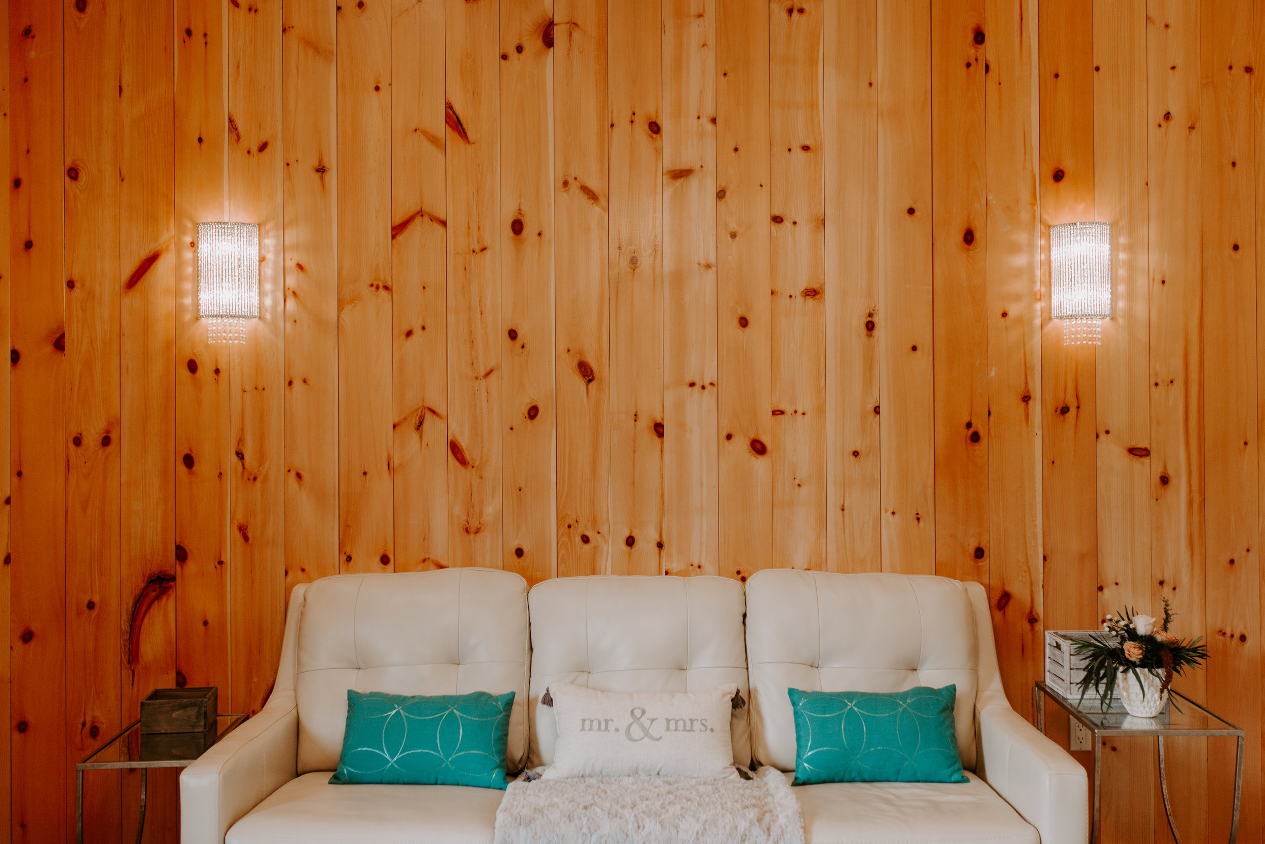 pine walls in bridal suite at Country Lane Lodge with white sofa and blue pillows sitting on couch that say Mr. and Mrs.