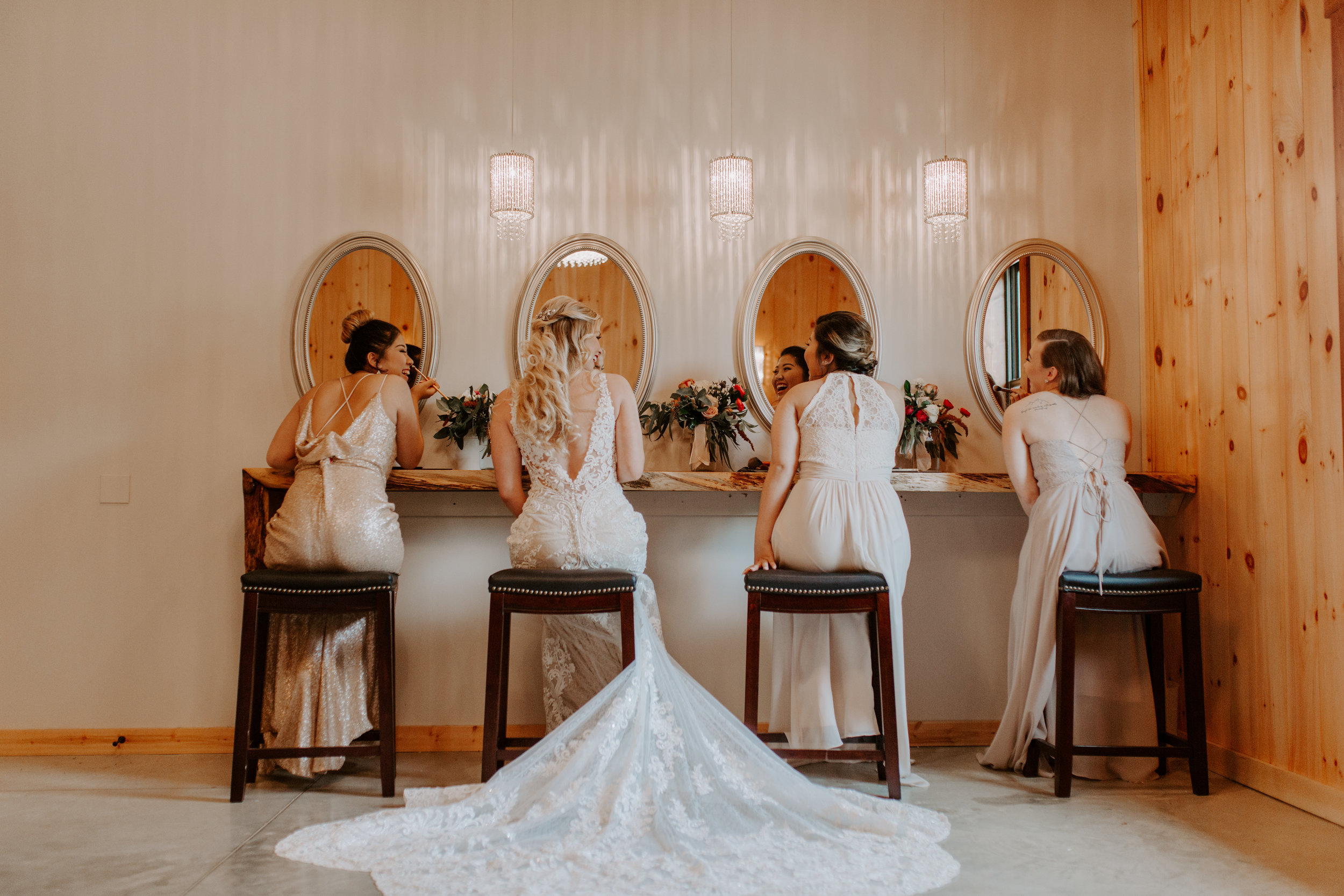 bride and bridesmaids getting ready in bridal suite , putting on makeup, long train of wedding dress is seen with lace and decorative trim, girls looking in the mirror and getting ready for wedding
