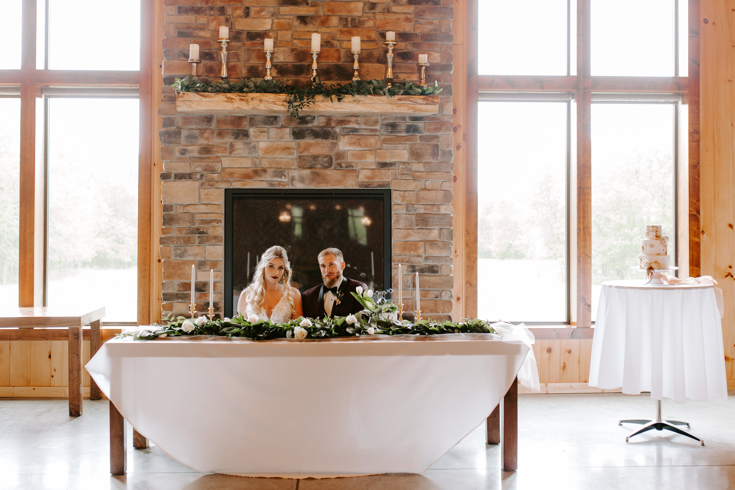 bride and grrom sit at kings table in front of stone fireplace at iowa wedding venue with rustic barn look