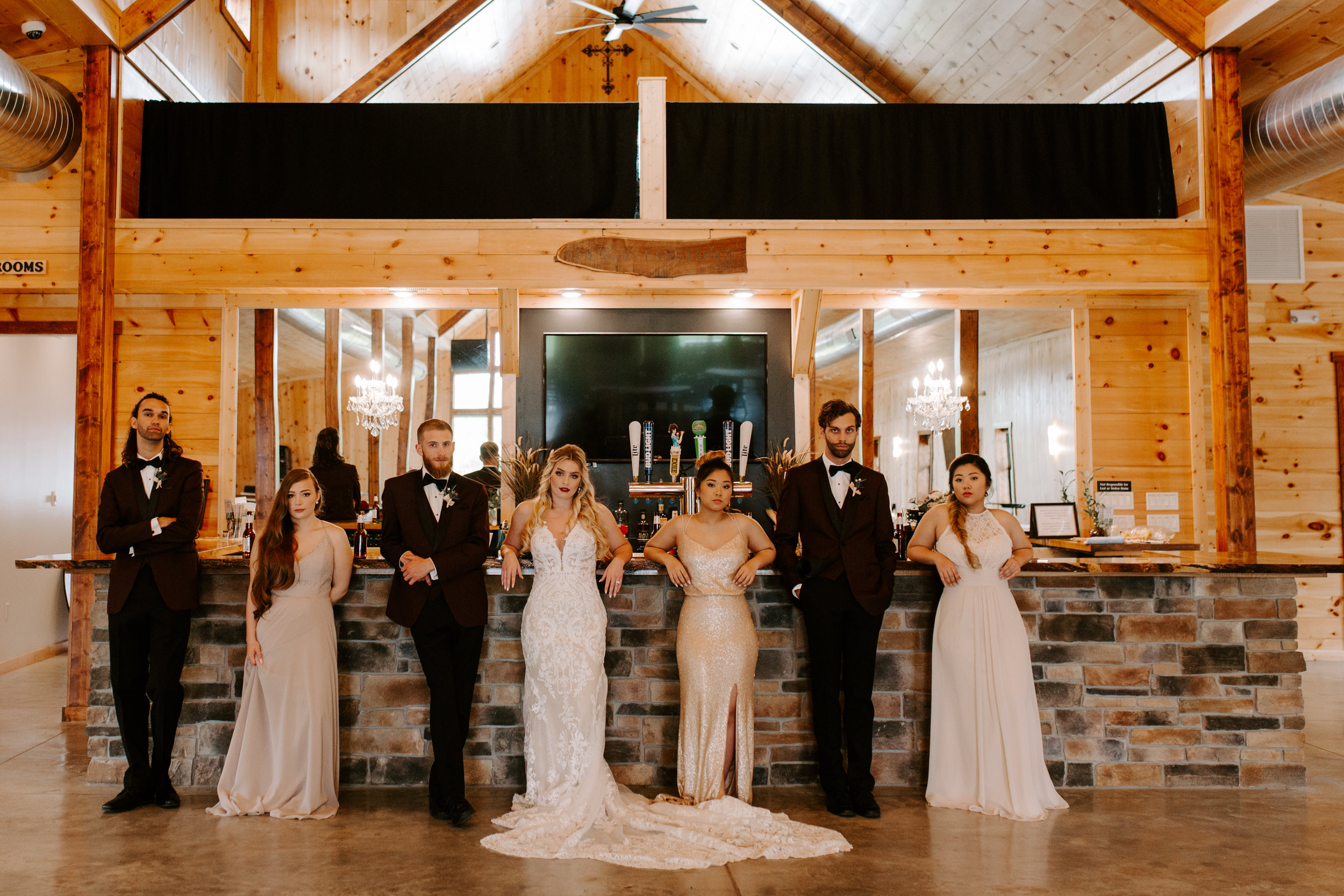 wedding party is relaxing and having a drink at the bar at Country Lane lodge in Adel iowa, bridesmaids are wearing blush, grey and gold dresses