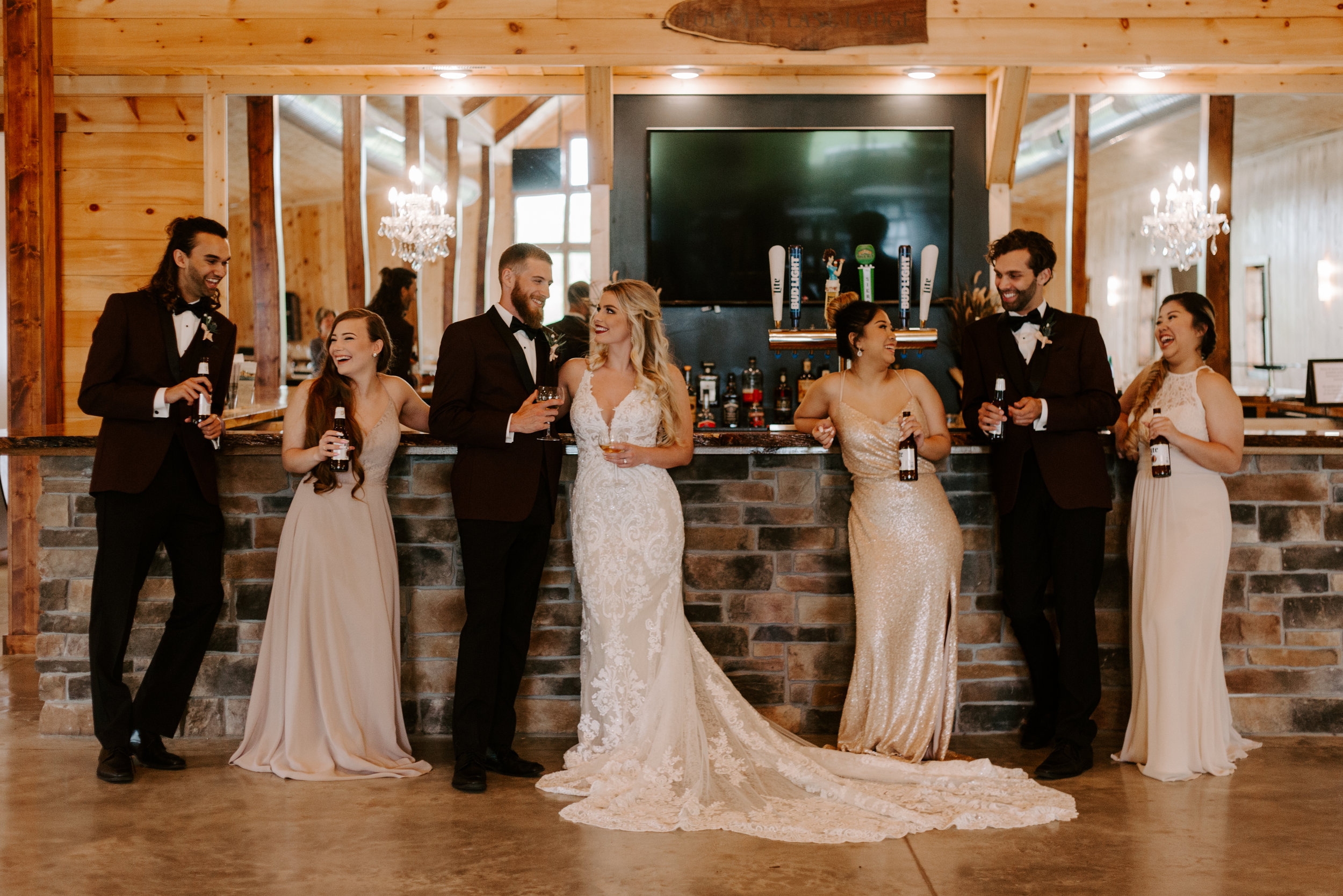 bridesmaids and groomsmen relax with bride and groom at the large bar area at Country Lane Lodge , men wear dark burgundy tuxes with burgundy vests, and black bow ties
