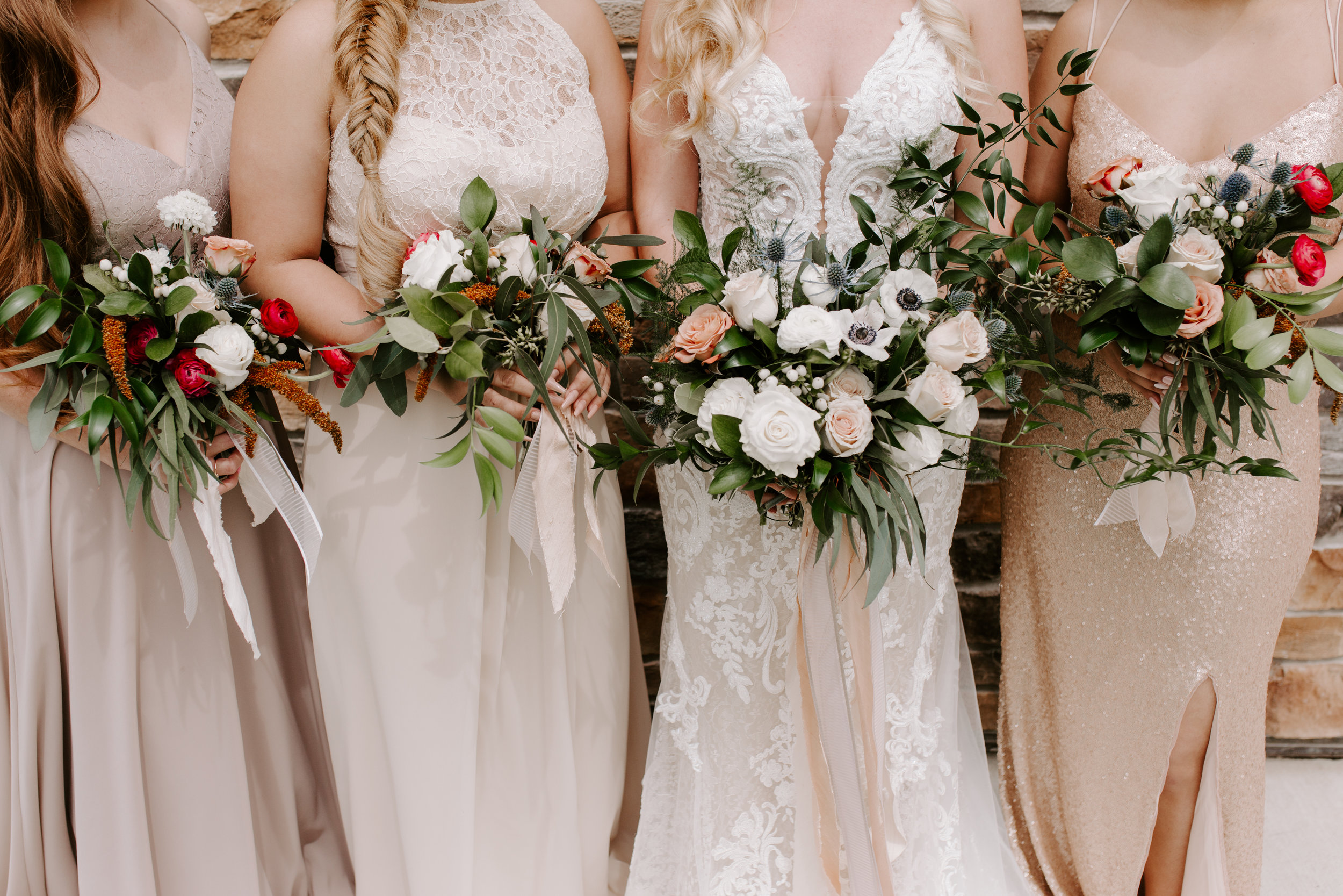 bridesmaids outside of wedding venue in Adel Iowa holding cream, white, and blush wedding bouquets, streamers of blush ribbon hanging down, bride wearing lace couture wedding gown with lace overlay and blush under tones, bridesmaids wearing blush and gold dresses