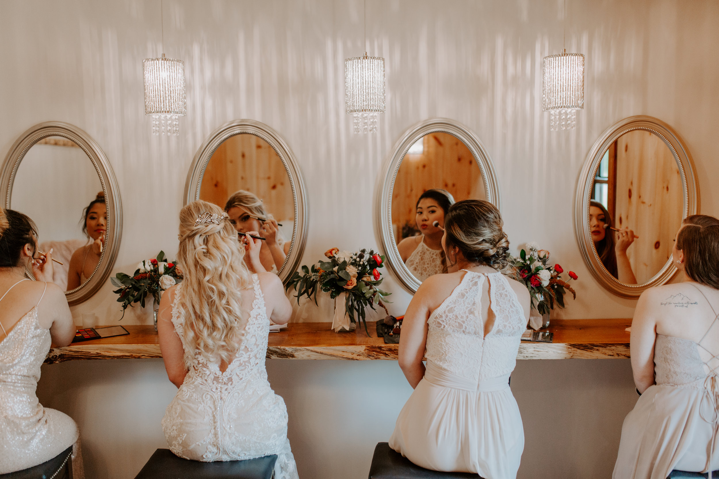 Bridesmaids getting ready in front of mirrors at wedding venue, Country Lane Lodge in Adel Iowa, wearing blush, grey, and cream designer gowns from West Des Moines Iowa