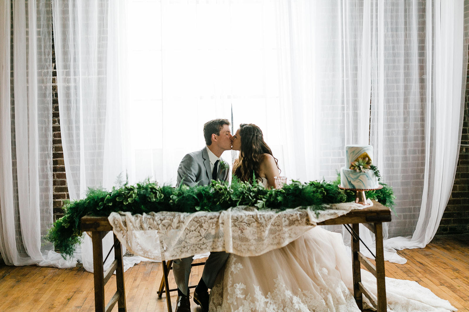 Wedding couple kisses while sitting at a large wooden table with a greenery garland in front of them and a wedding cake with a marble finish. Lace edges the couture wedding gown from Des Moines Iowa, colors of the tux are steel grey and blue, brick walls are in the background of the studio space