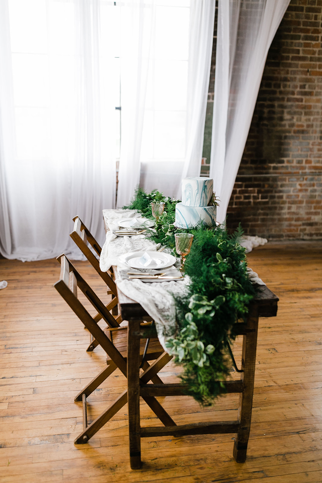wooden table sits on wooden floor of photography studio in downtown Des Moines iowa, lush greenery rests on the edge of the table with eucalyptus, white sparkling china and vintage lace decorate the head table for the bride and groom