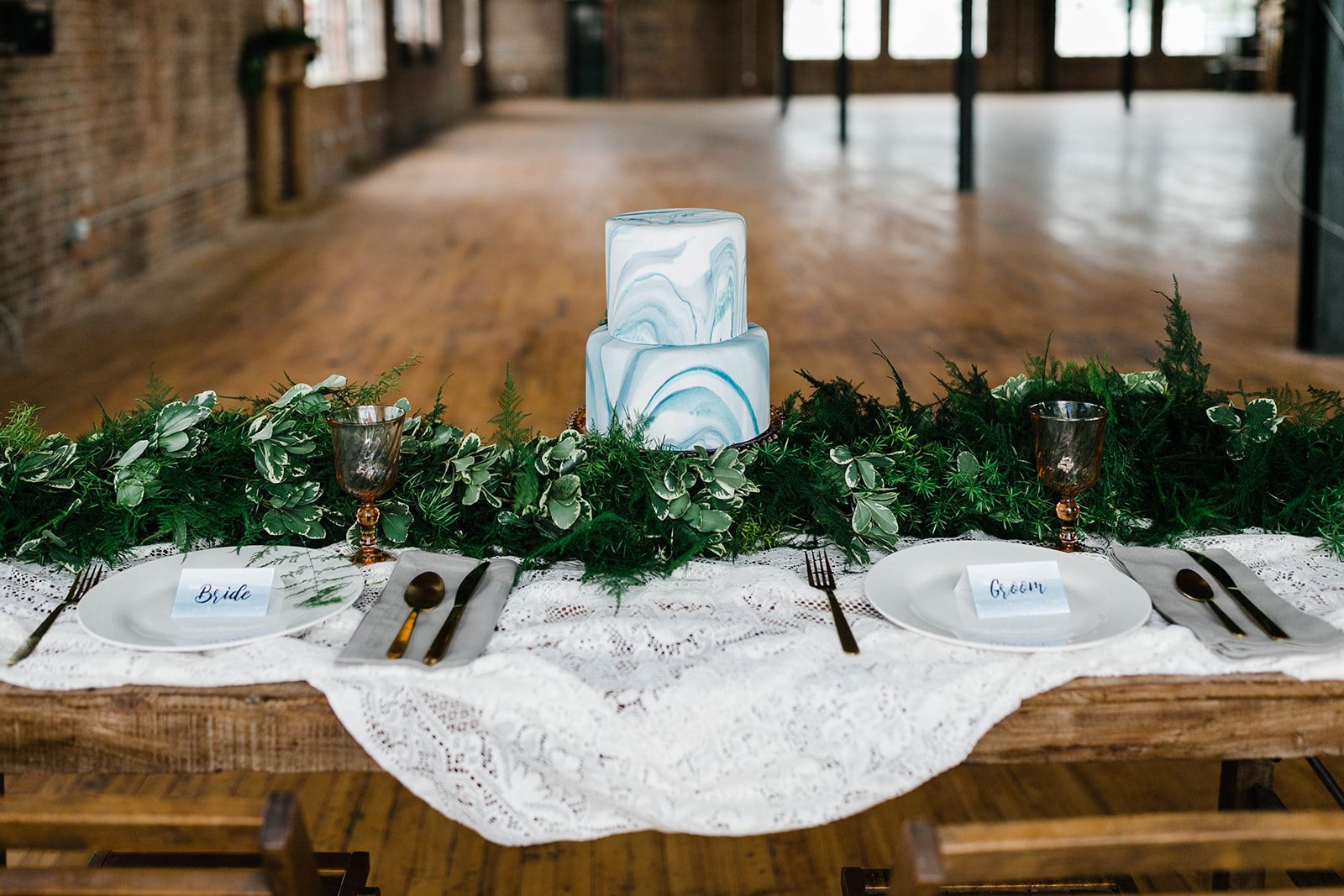 wooden table on floor of vintage building in downtown Des Moines, Iowa, marble motif is seen on 2 tier wedding cake, lush greenery from Lavender Blue rests on the table of fine white china