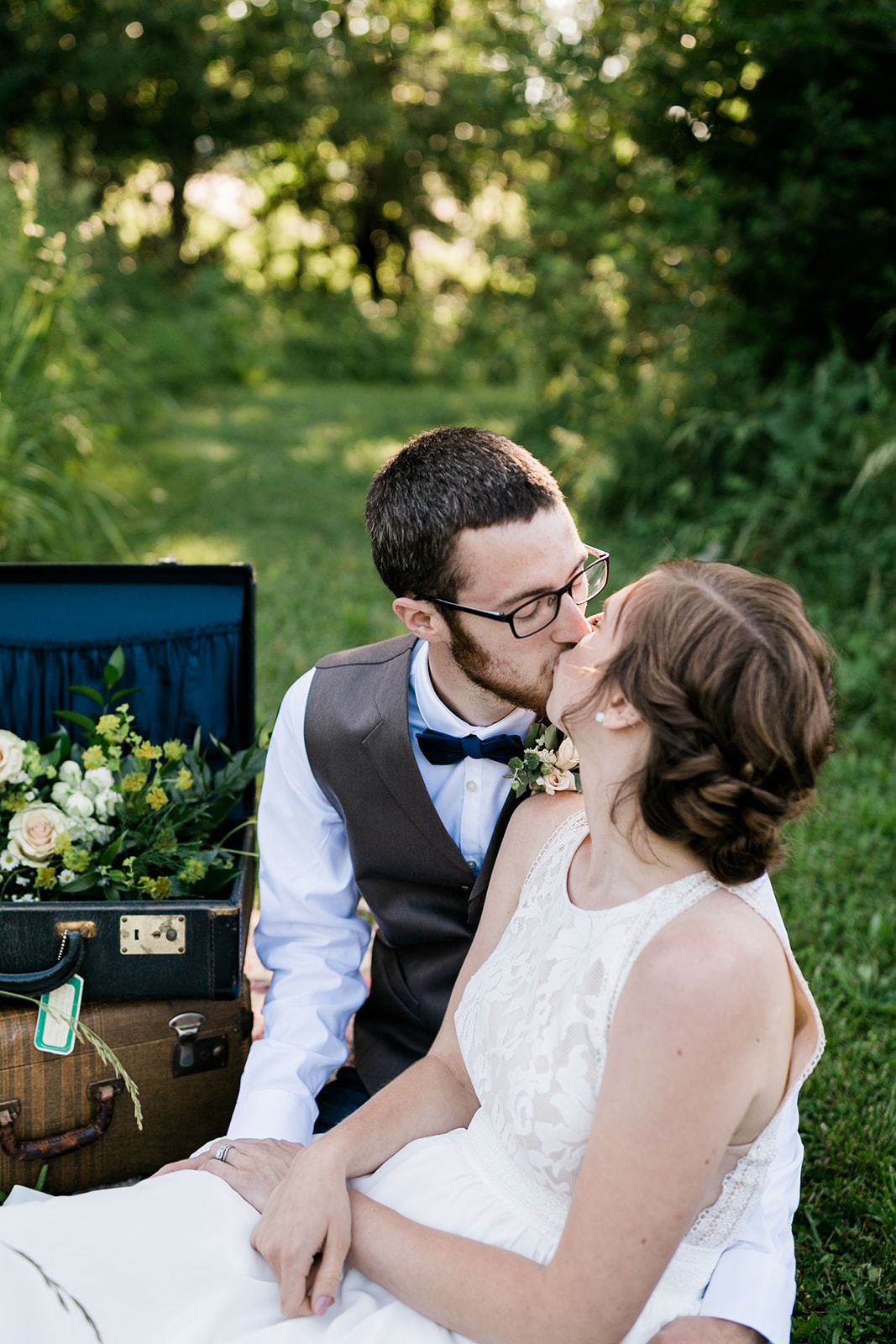 Wedding couple in photo shoot in Des Moines Iowa, sitting on yellow blanket, and kissing, vintage style props sit in the background