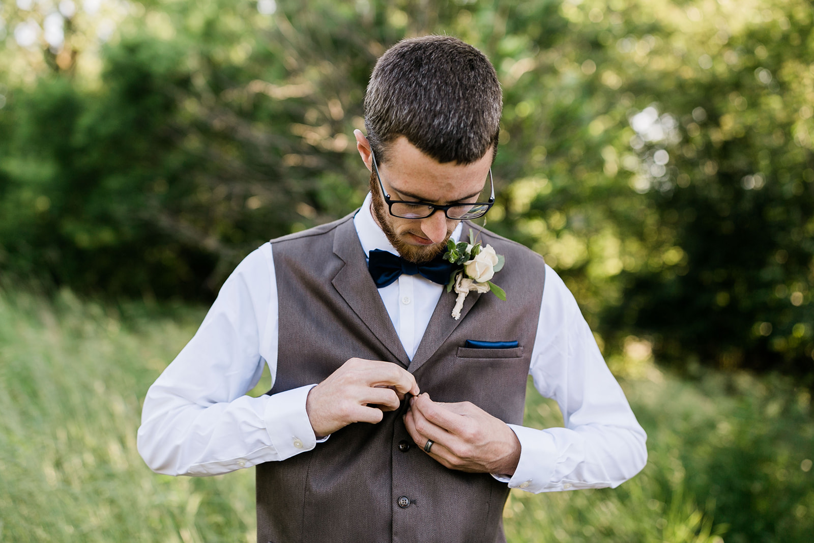 wedding groom in photography shoot in Des Moines Iowa, buttoning his brown tuxedo jacket with rose boutonniere , tied with blush satin ribbon
