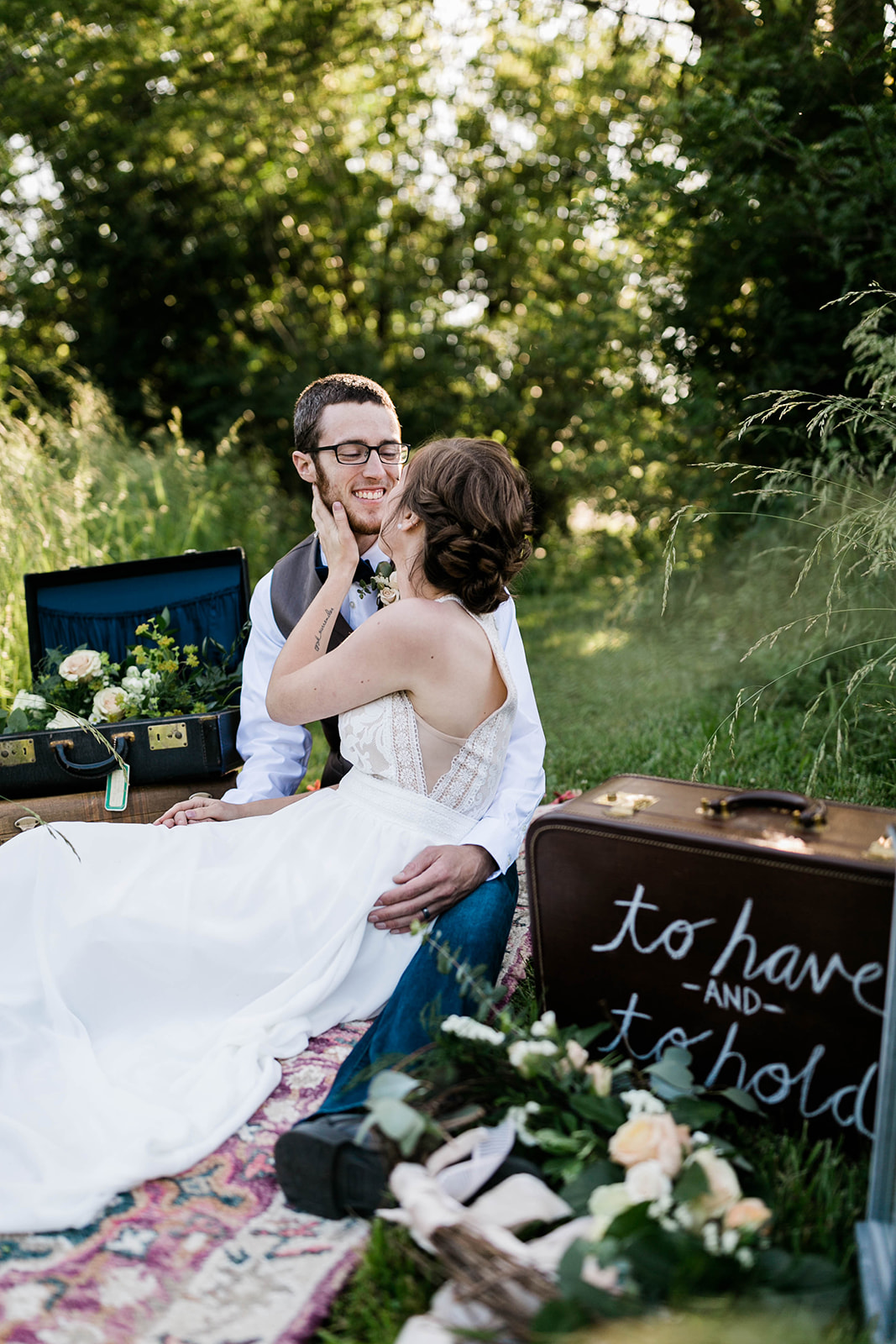 Couple looks at each other in love, at vintage travel elopement wedding in Des Moines Iowa with leather vintage suitcases and floral accents of blush and blue