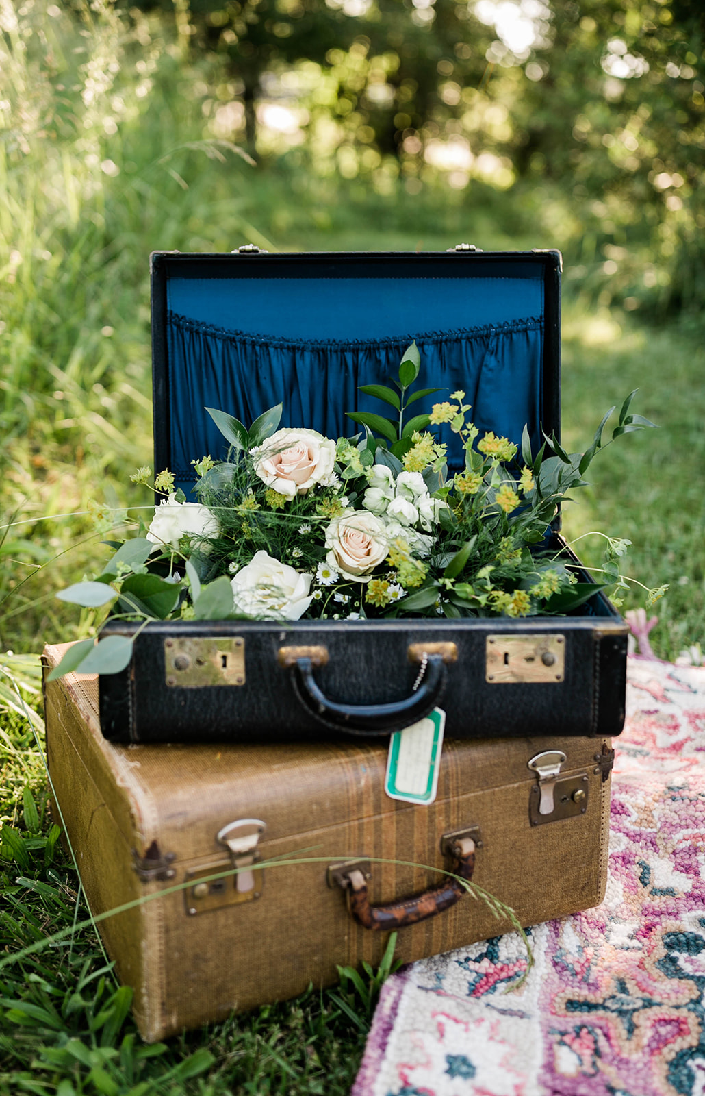 Vintage leather suitcases at an outside photo session of a travel theme wedding in Des Moines Iowa, with flowers in the suitcase of blush and cream with roses and wildflowers