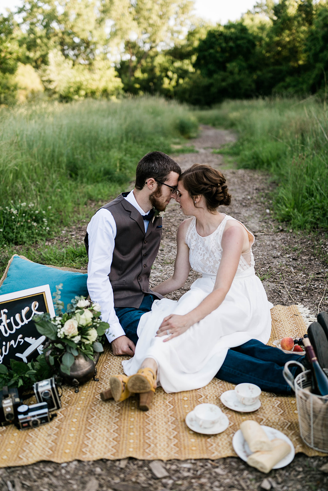 wedding couple in styled wedding photo session with travel themed accents and flowers in silver tea pot in Des Moines iowa
