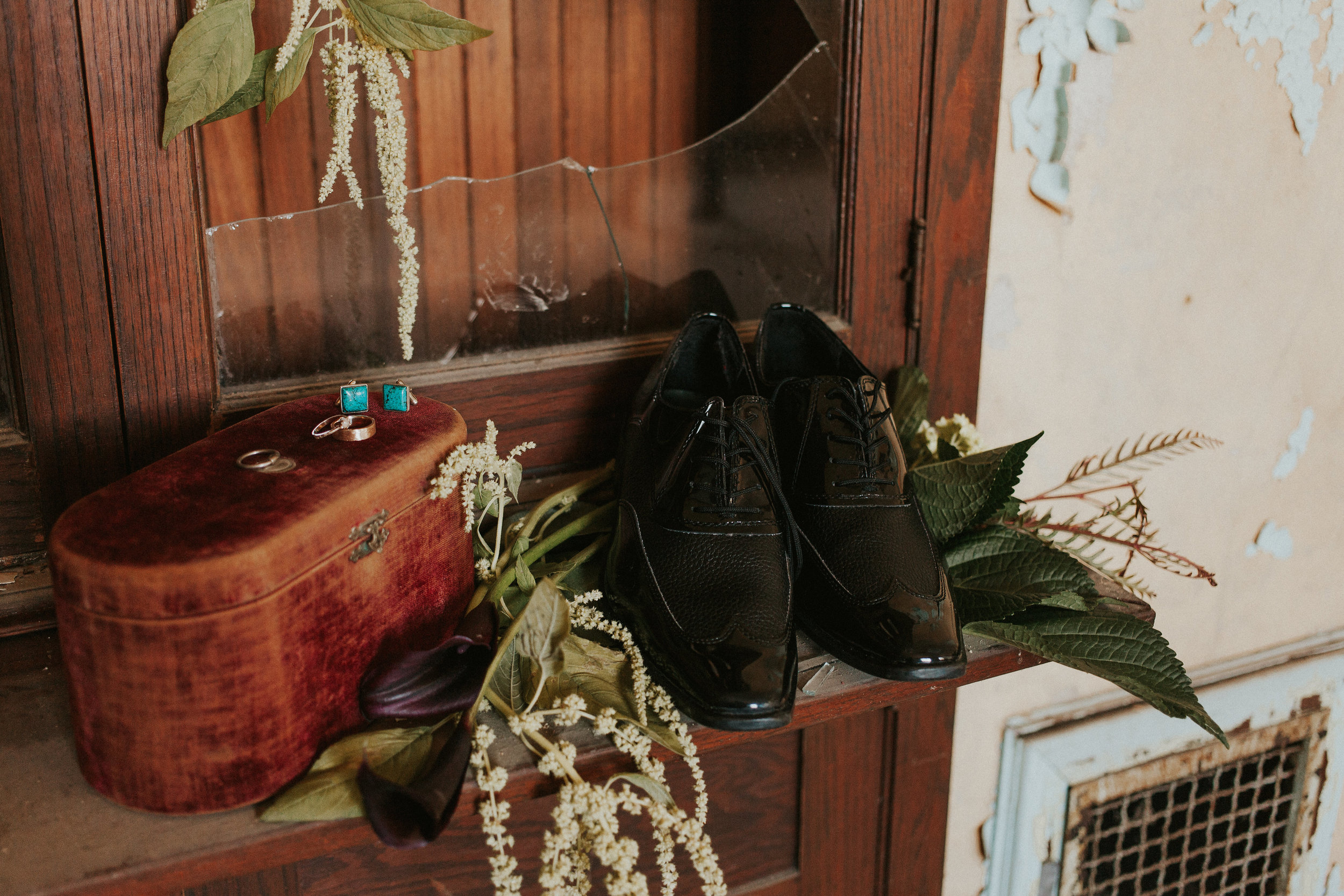 gothic theme photo session with black shoes and crafted wedding rings displayed on an old vintage suitcase, with hanging flowers and greenery in the background and candles
