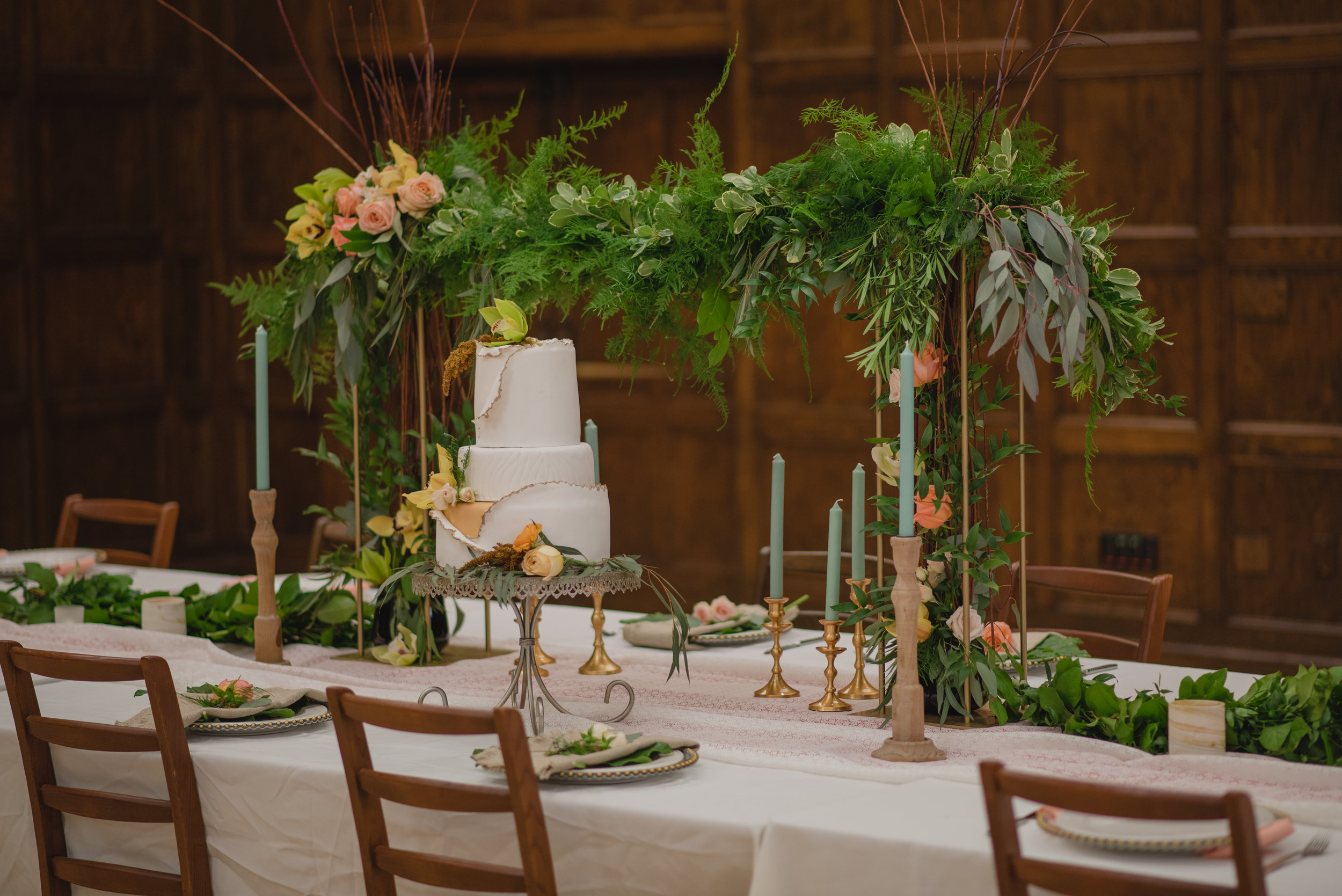 Flower garland sits on table with white linens inside of a wedding venue in Ames Iowa, with a white wedding cake .Floral accents of orchids and blush roses with gold candlesticks and green candles