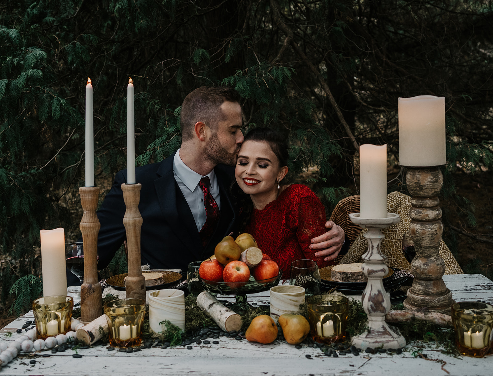 wedding coupe in woodland setting with large wooden rustic candles, birch wood sticks, and colorful apples and pears