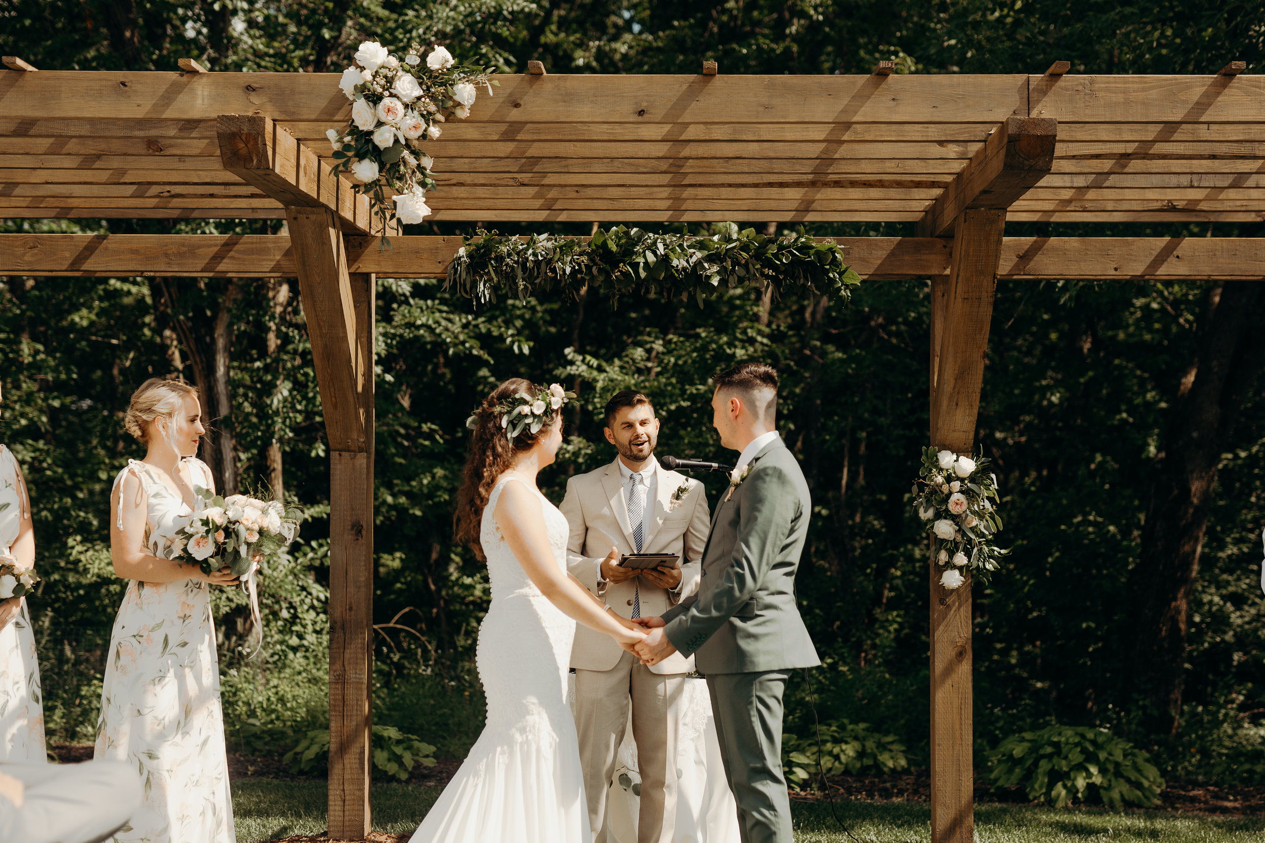 Bride in white lace dress with blush and white floral crown, from Lavender Blue Floral. Groom in sage green tux with floral tie in blush. Bride and groom stand under arbor with floral arch in white and blush. Bridesmaid stands by bride in blush and light green floral long dress.