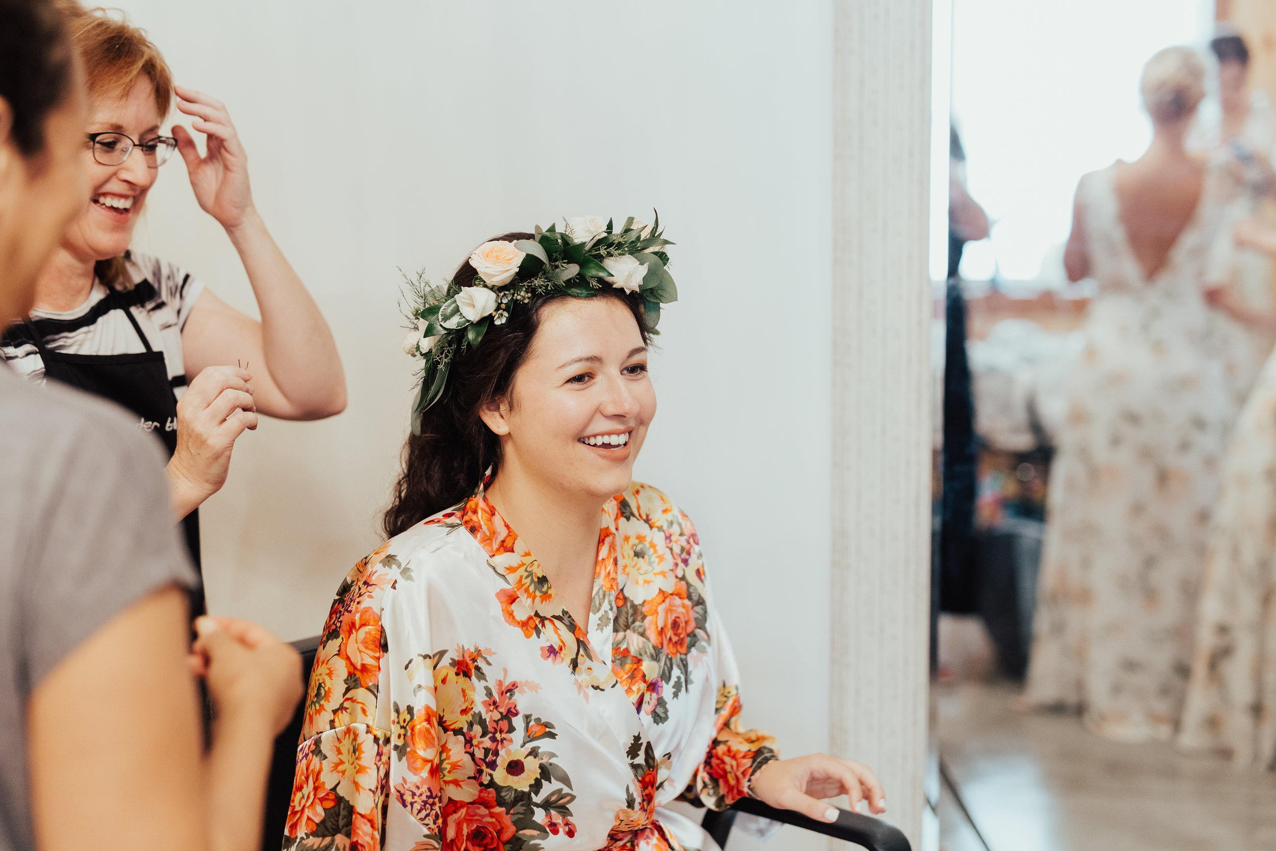 The bride smiles as she sees the image of herself in the mirror with her freshly placed flower crown by Lavender Blue. Lots of bobby pins were needed to secure the crown in her beautiful thick locks of dark , curly hair.