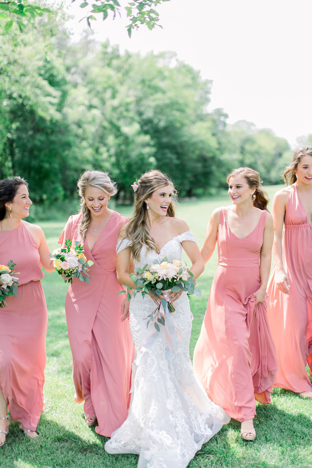 Iowa bride in lace couture gown from Des Moines Iowa, bridesmaids in blush dresses, holding bouquets of blush, white and apricot color roses with eucalyptus. Bride laughs and walks with bridesmaids at propoery in Adel Iowa