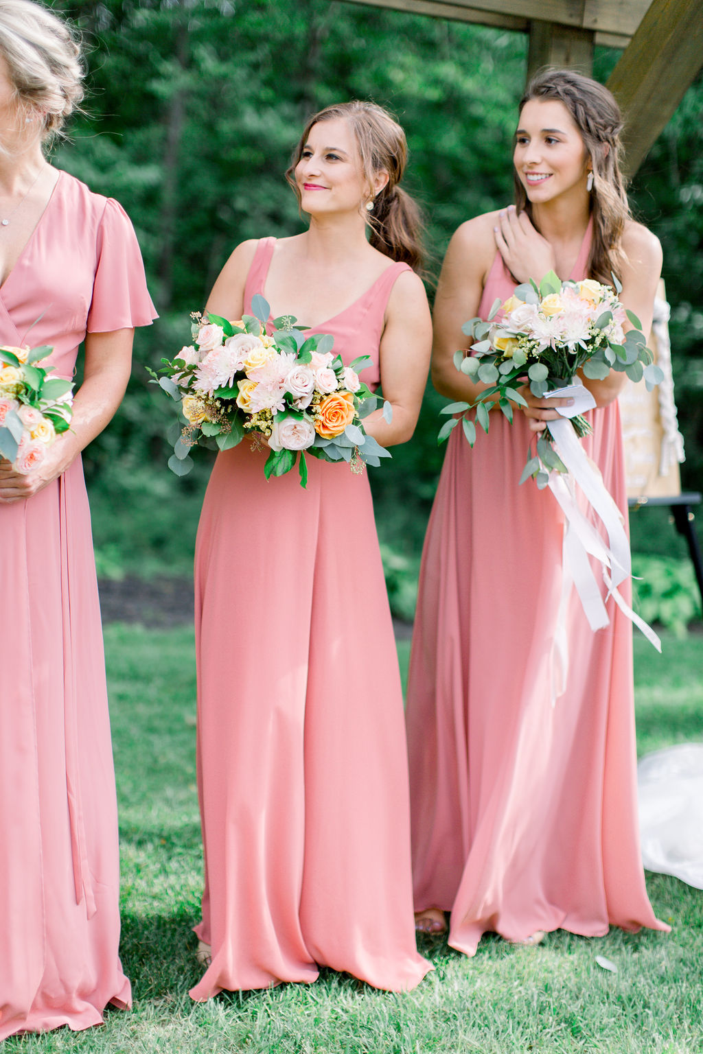 Bridesmaids look on , while bride and groom say their personalized vows at Country Lane Lodge, wearing long , blush gowns, all in a different style, each perfectly fitting their unique body type. Bridesmaids hold bouquets of cream, blush, and yellow flowers, with roses and a mixture of greenery.