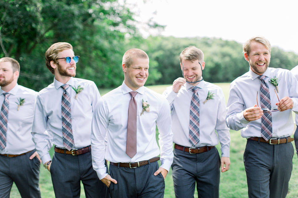 Groomsmen smile and laugh, while taking a stroll before the wedding ceremony, wearing dark grey pants with brown leather belts. Ties are coordinate, with the groom, Jeremy, wearing a light burgundy color and his gents in a plaid burgundy and blue print.