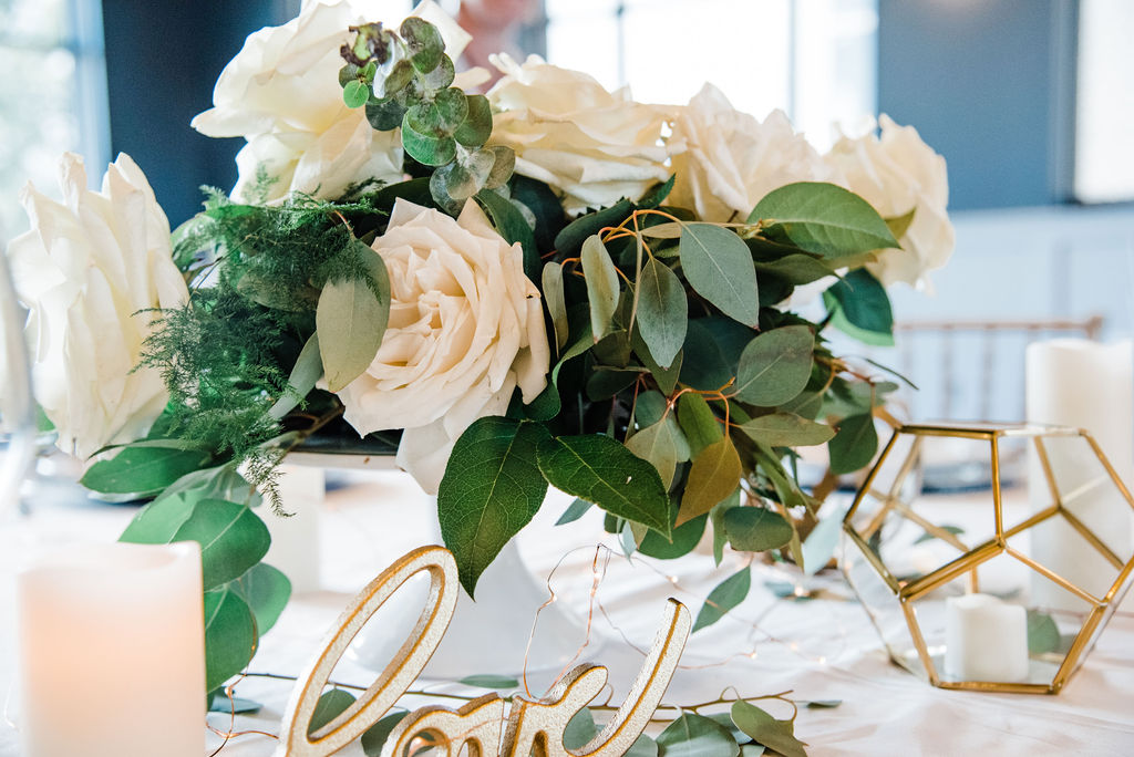 Floral arrangement of vanilla colored garden roses sits on a wedding reception table of white linens with gold accents. A gold candle holder and a 'love' sign sit on the elegant decorated table with sprigs of fresh greenery .