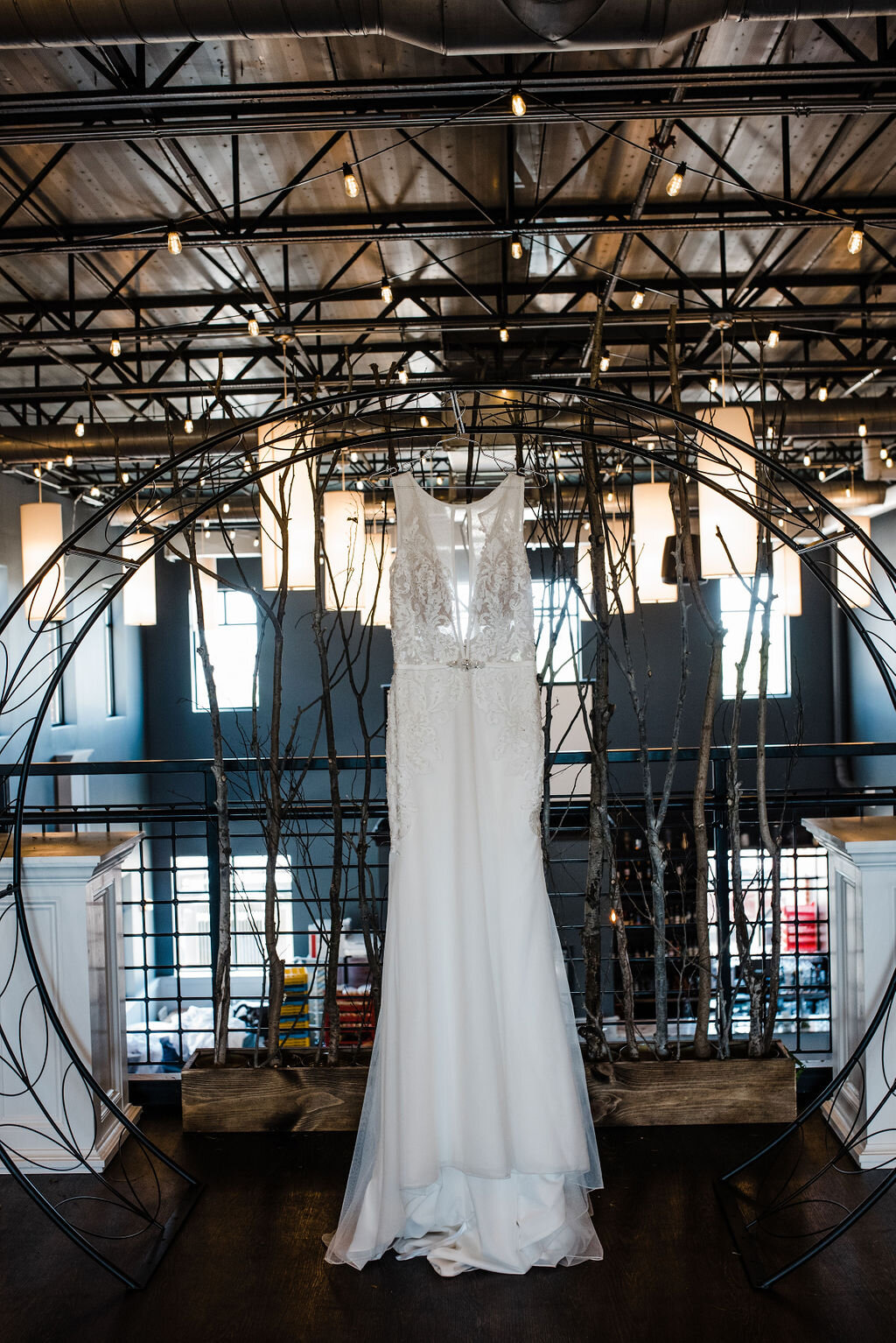 white wedding gown with long train and lace top has a sparkling belt. Wedding dress hangs from a Moon Gate arch on the upper level or a chic wedding venue in Ankeny Iowa. Slate grey walls make a striking backdrop to stark white wood trim and white wooden pedestals flank each side of the wedding arch.