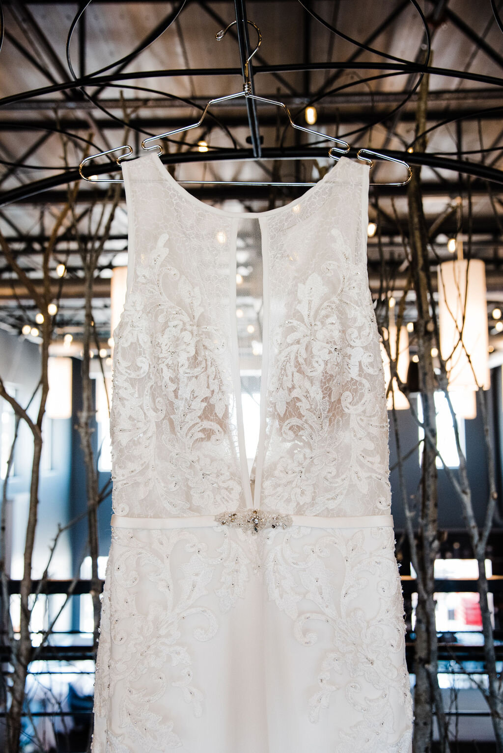 beautiful wedding gown hangs on a Moon Gate arch at a wedding venue in Iowa, a sparkling broach is at the waist, and overlays of scalloped lace designs or on the bodice and part of the long flowing skirt