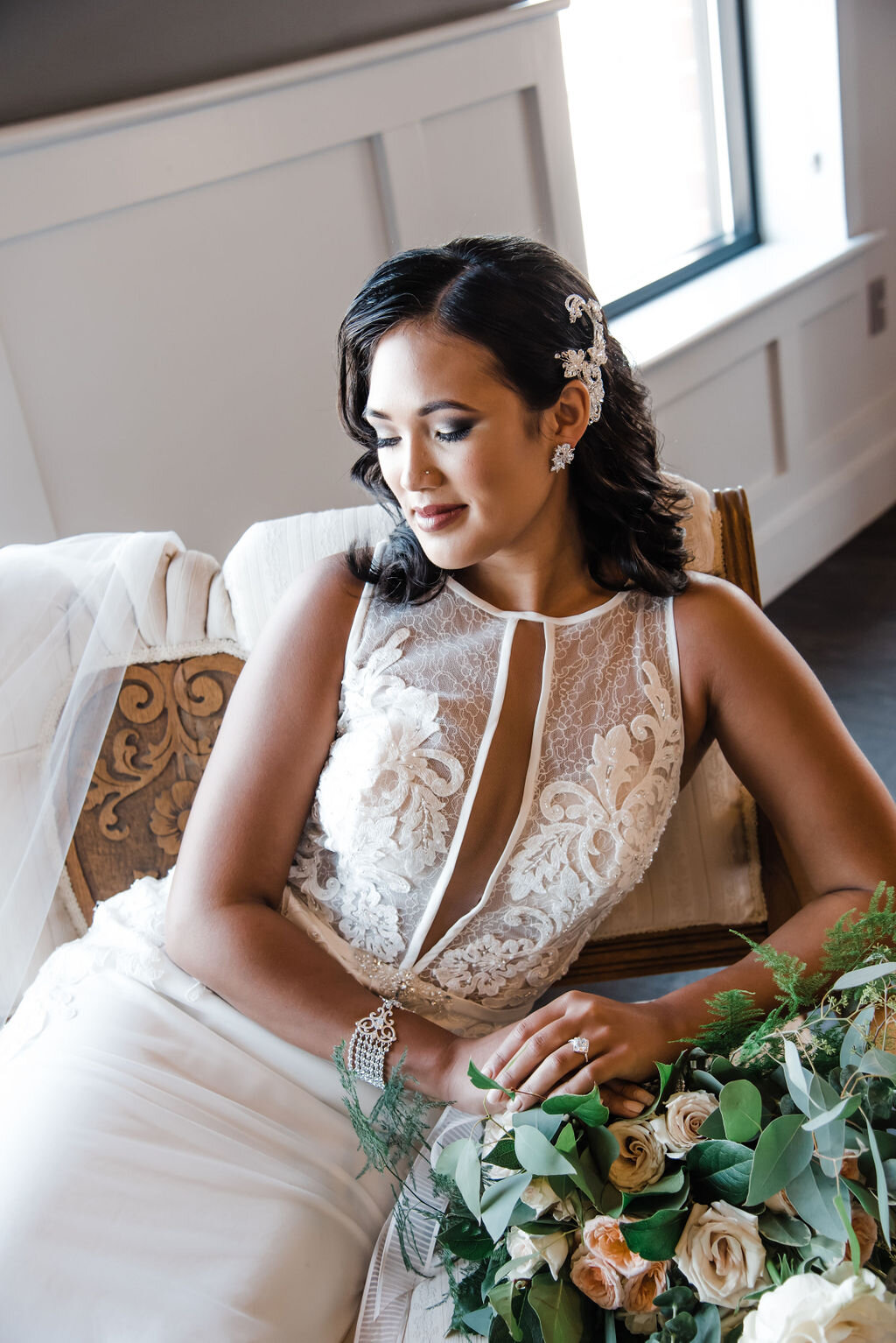 bride rests on vintage French settee, with carved wooden design on back of seat, with lace and satin wedding gown. Wedding bouquet sits next to bride with blush, apricot, and cream colored roses.