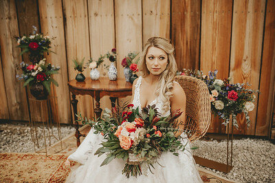 Bride in white lace gown sits on brown wicker boho chair, holding large bouquet of blush and pink flowers with eucalyptus at Wedding venue in Iowa
