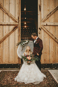 Bride in white lace wedding gown, sits in white wicker boho chair with large bouquet of blush and white, and chair is decorated with flowers and eucalyptus , in a boho style