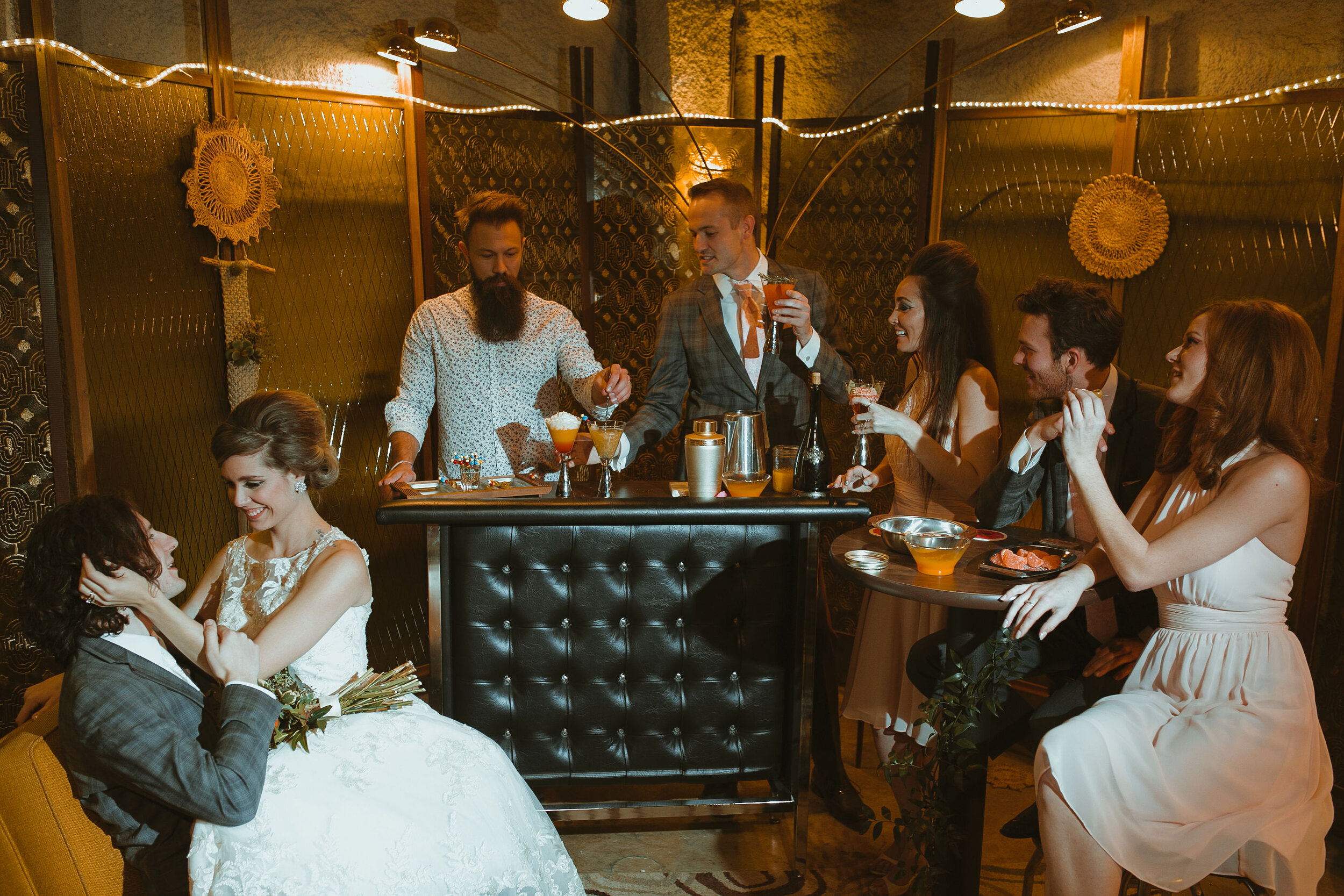Mid century modern setting for wedding elopement in Iowa, vintage mini bar with bartender and bridal party toasting drinks with bride and groom looking at each other in chair