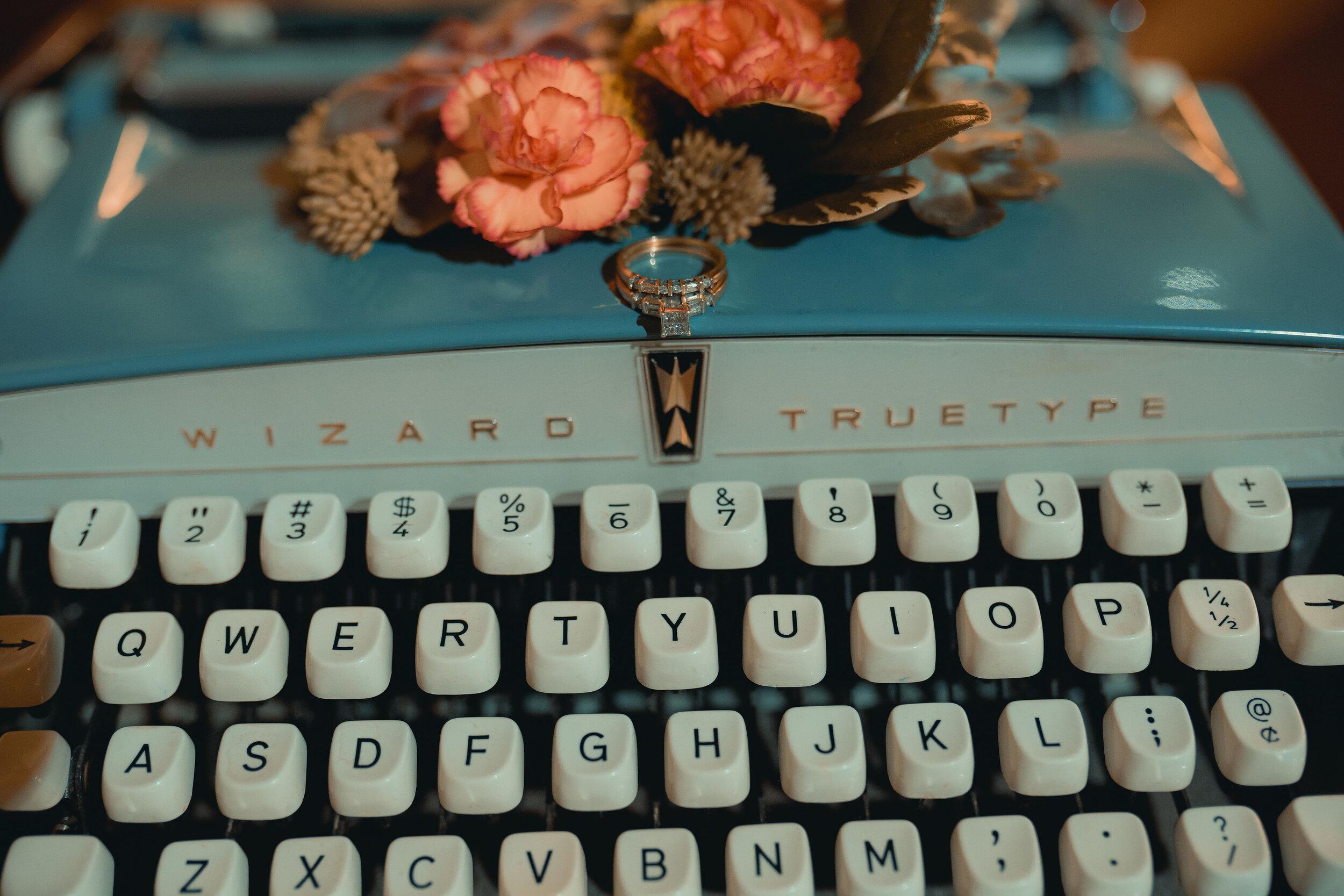 vintage typewriter displays wedding ring on blue typewriter wedding rental, with blush and green floral accent on top