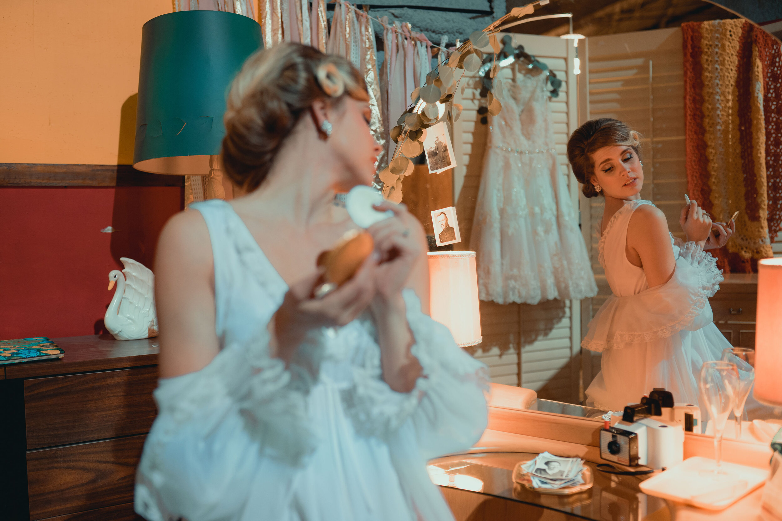 bride in vintage nightgown looks into mirror on mid century modern dresser, powders her nose, with vintage hair style