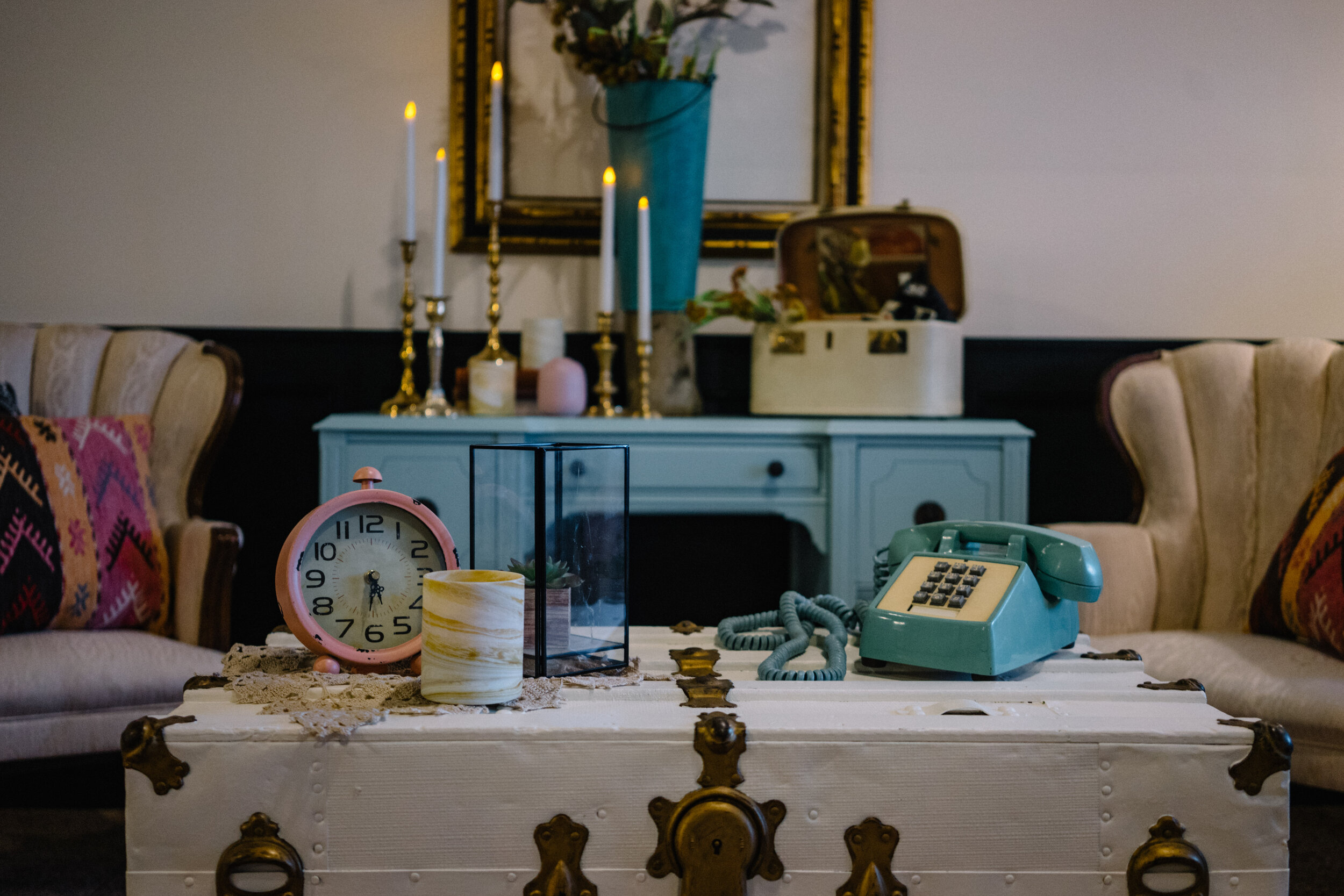 vintage style photo set up for wedding reception with blue vintage dresser, gold picture frame and mid century modern blue telephone and white antique upholstered chairs