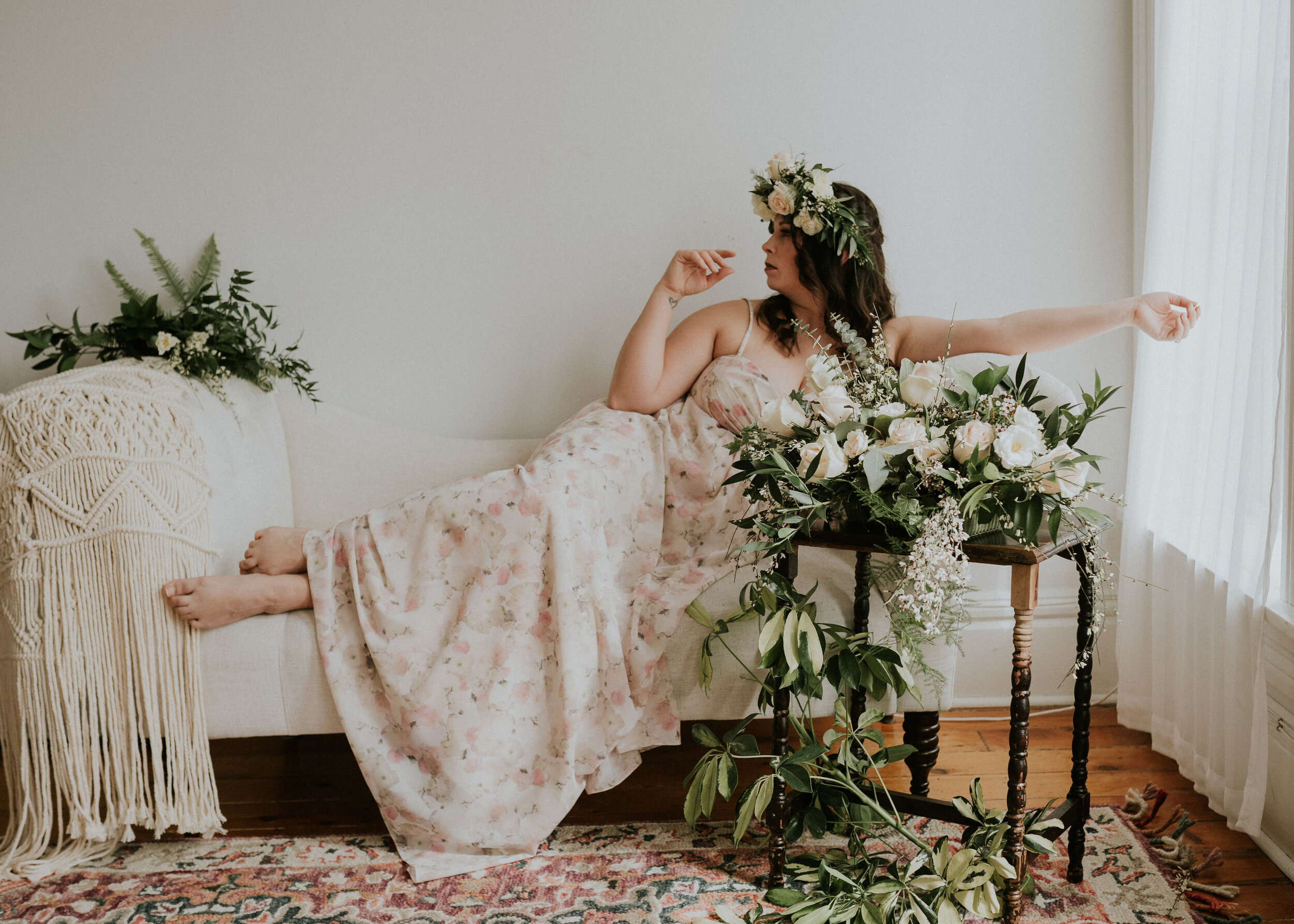 maternity styled photo shoot with woman in floral strapless gown, with macrame decor on white settee, white and cream floral arrangement and greenery rest on wooden vintage table, model wears a floral crown