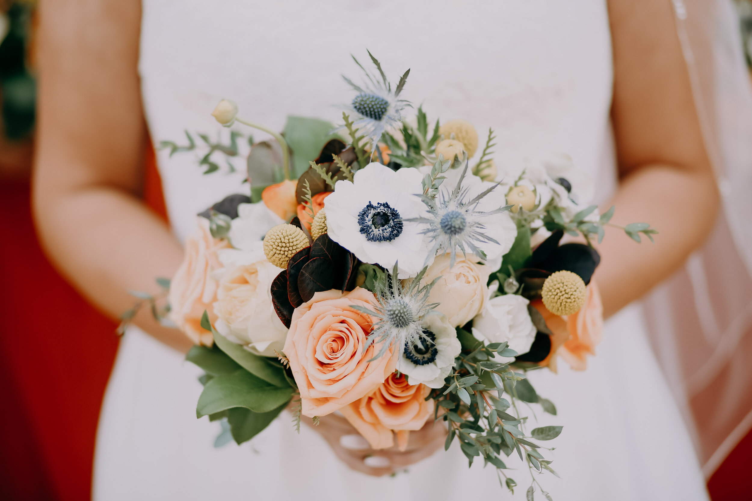 West End Salvage wedding in Des Moines iowa, bride with bouquet of coral and blue flowers with poppies and orange roses, and eucalyptus at vintage wedding event in Des Moines Iowa