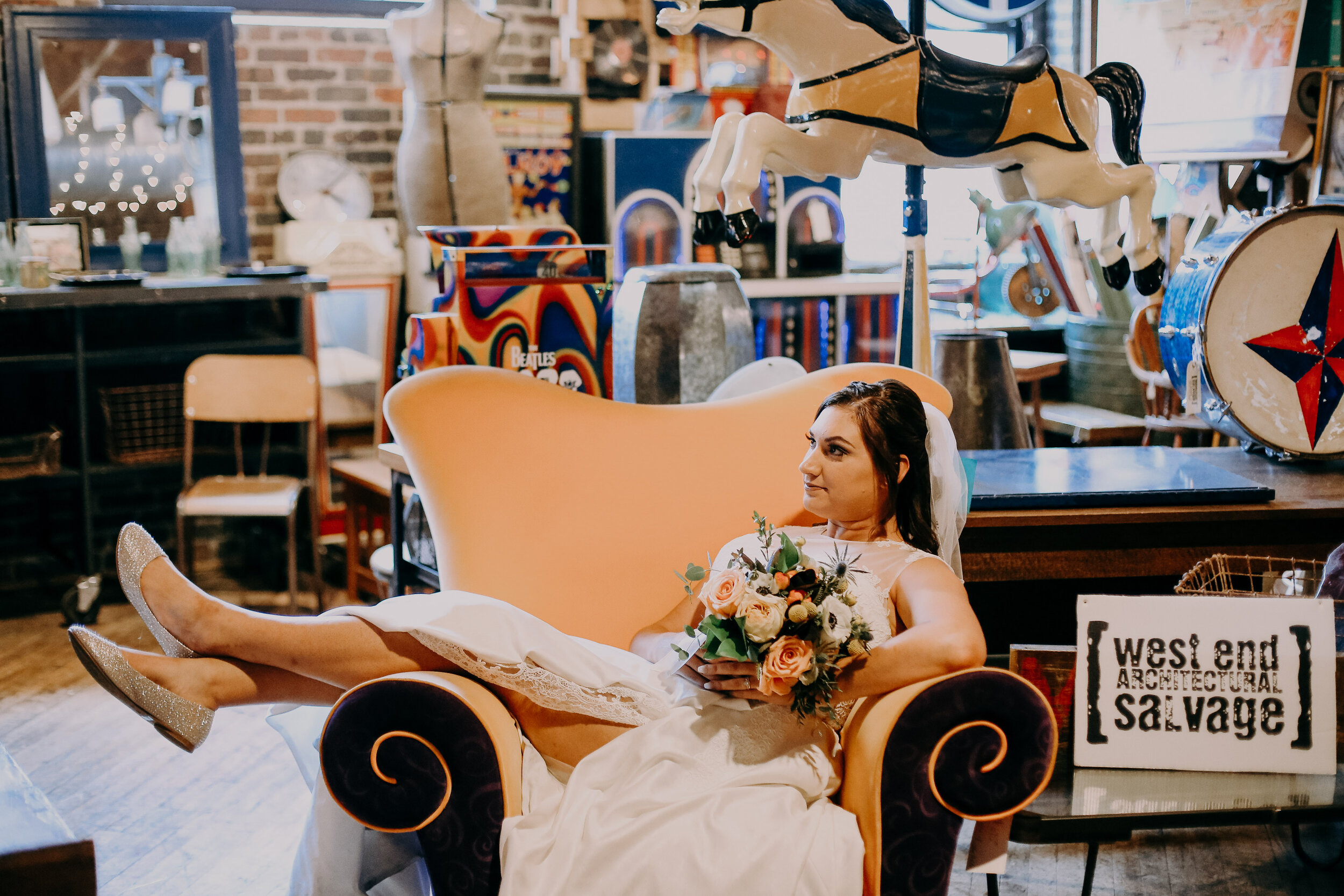 wedding at West End Salvage in Des Moines Iowa was the setting for this happy and relaxed bride as she sets her feet up on a designer black and orange chair, with vintage rocking horse and mirrors in the background
