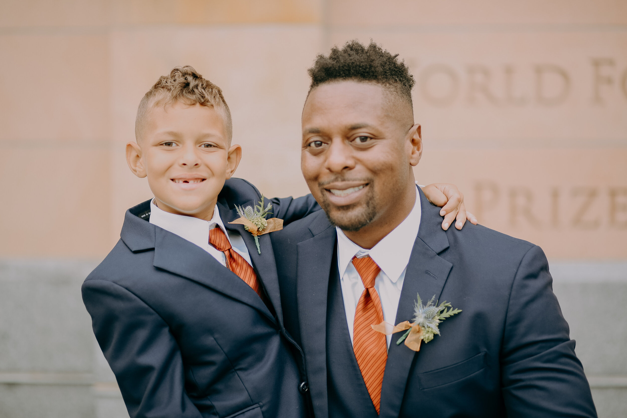 groom and ringbearer pose in dark grey tuxes from Skeffingtons formal wear in Des Moines Iowa with rust colored stripe ties and a boutonniere of blue thistle and greenery with a burnt orange ribbon