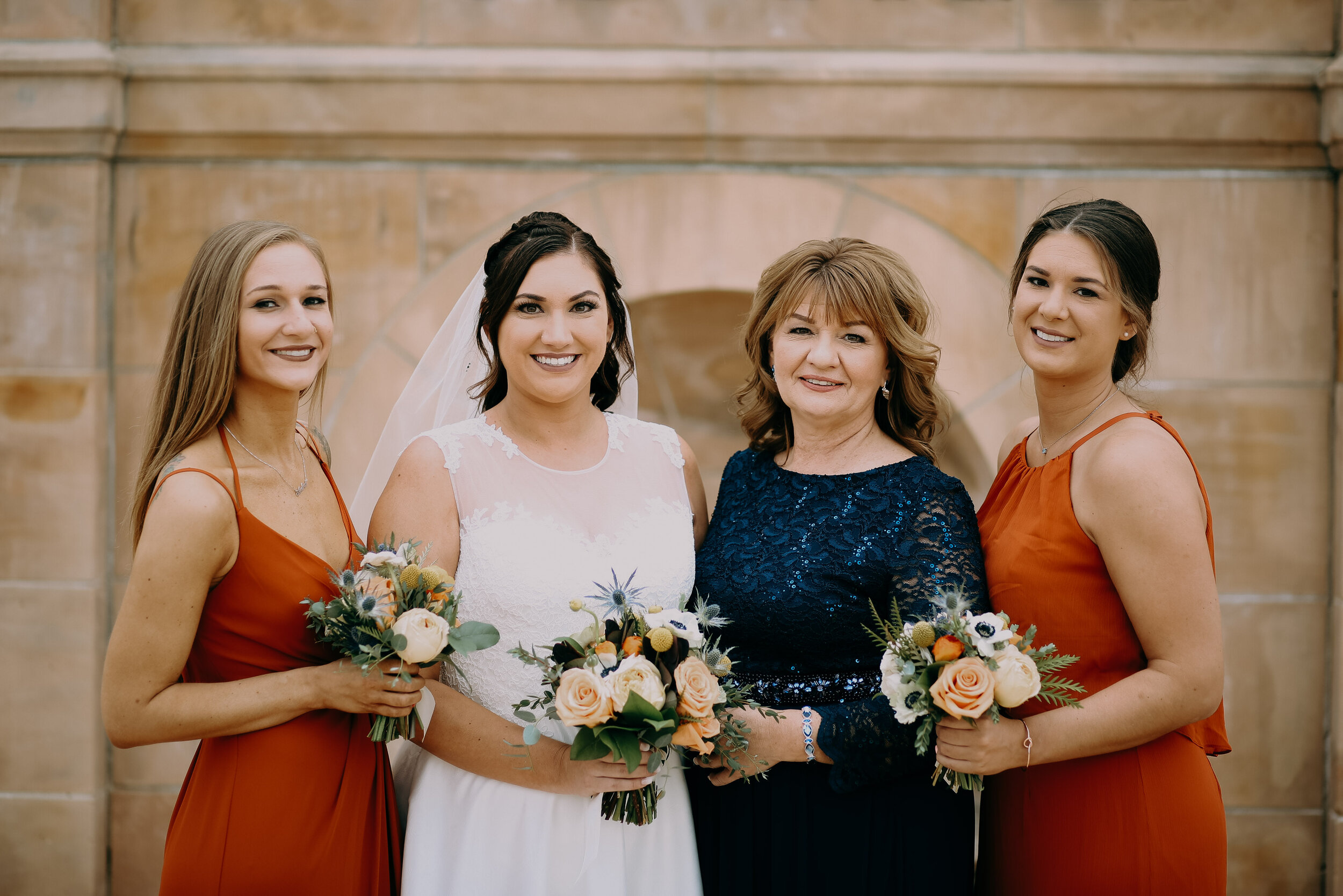 bridesmaids in rust colored halter wedding dresses pose with the mother of the bride in dark navy and lace formal dress, while holding bouquets of blush roses and white poppies with eucalyptus