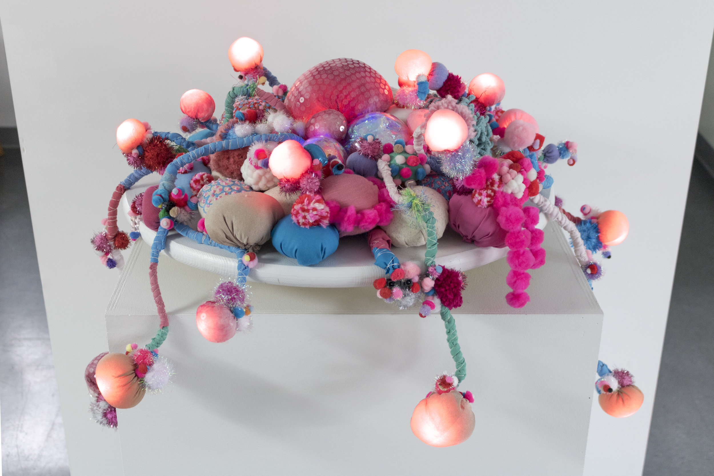 This collaboration between Lucas and Jan uses Arduino, coding, LEDs, and a distance sensor to give Jan's emroidery-hoop growths a bioluminescent quality. The creature has a glowing center that gradually pulses faster depending on the viewers distance from it. When the viewer is at a close enough range the tentacles all begin to light up in examination. Image courtesy of Lucas Stiegman.